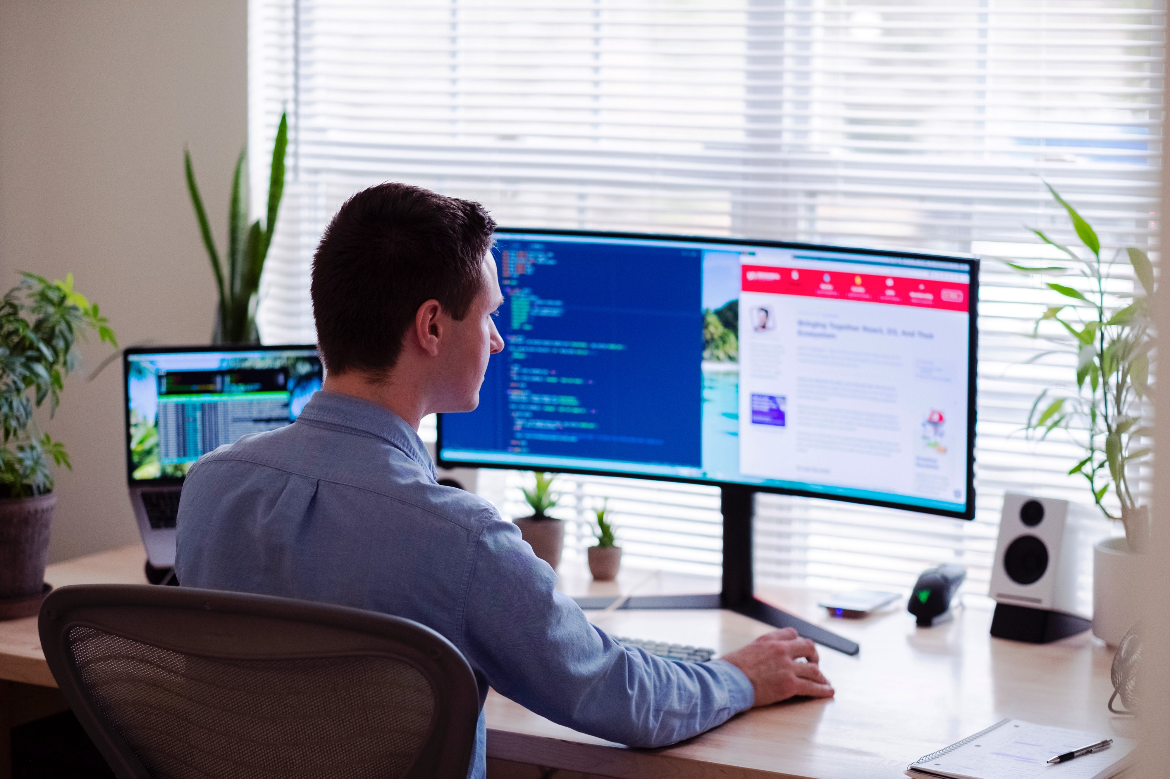 A professionally dressed man works at home with double computer screen and laptop on his desk with plants facing window