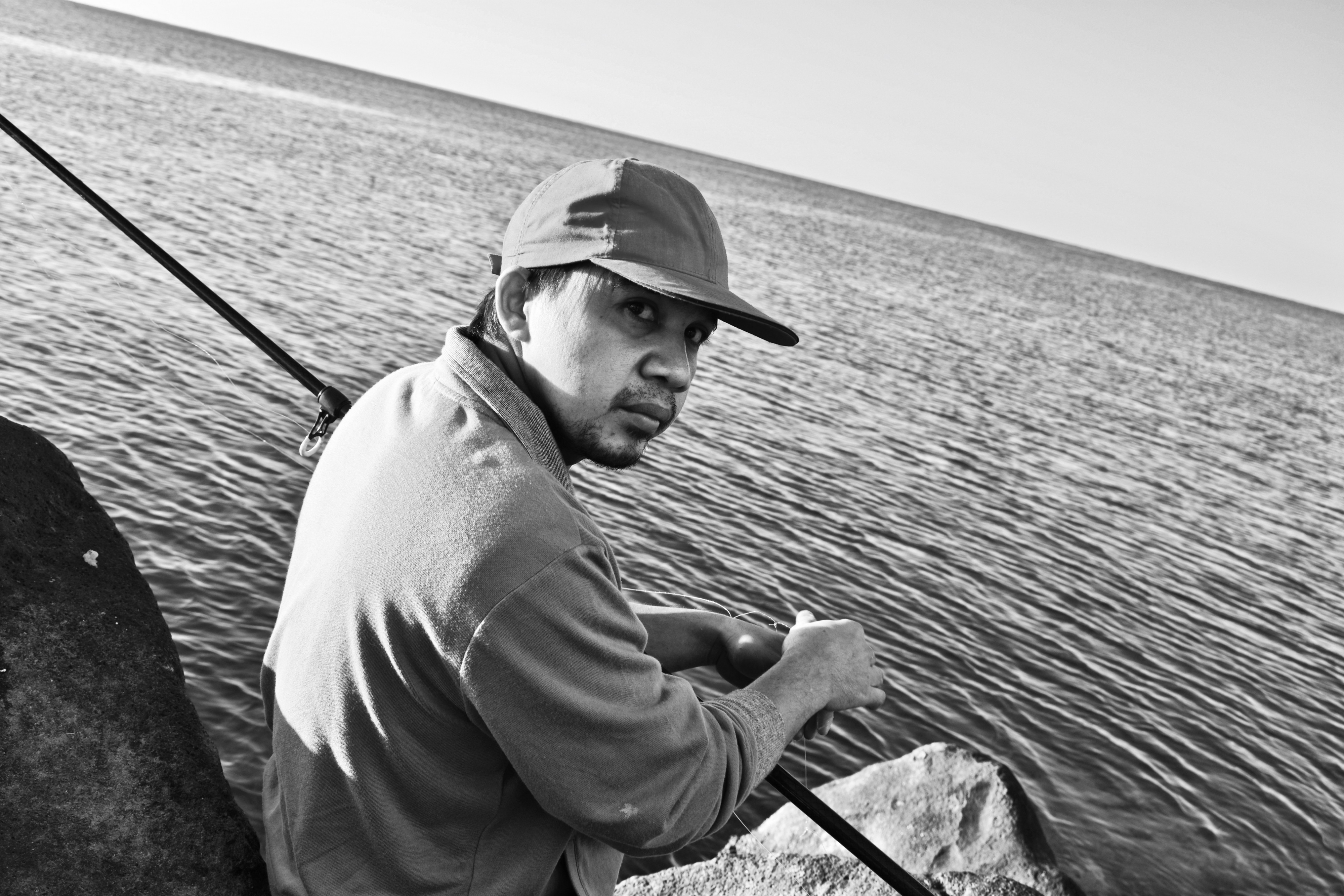 A father catching a fish in the bay