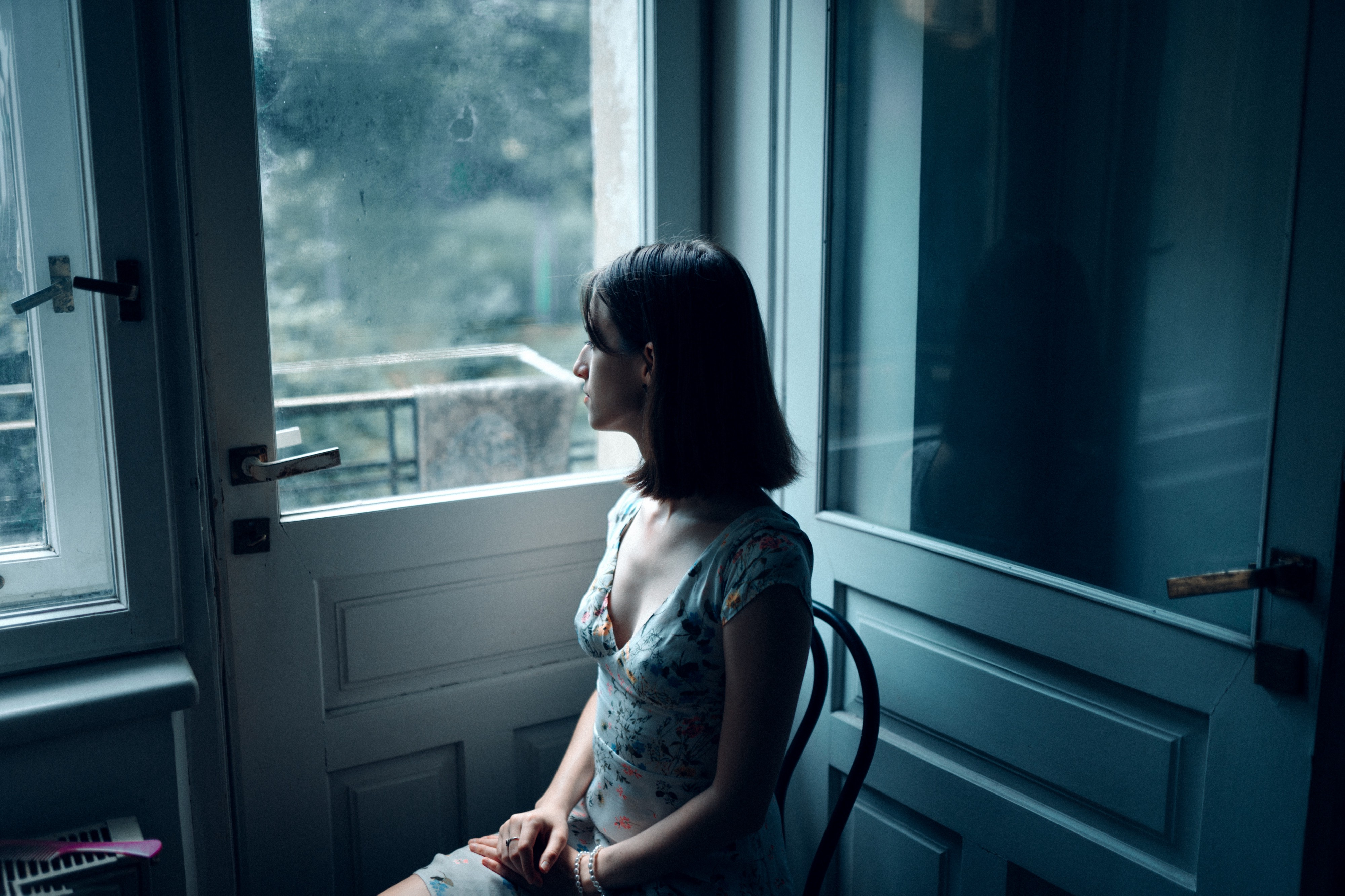 A woman sitting on a chair in solitude gazing out of a window.
