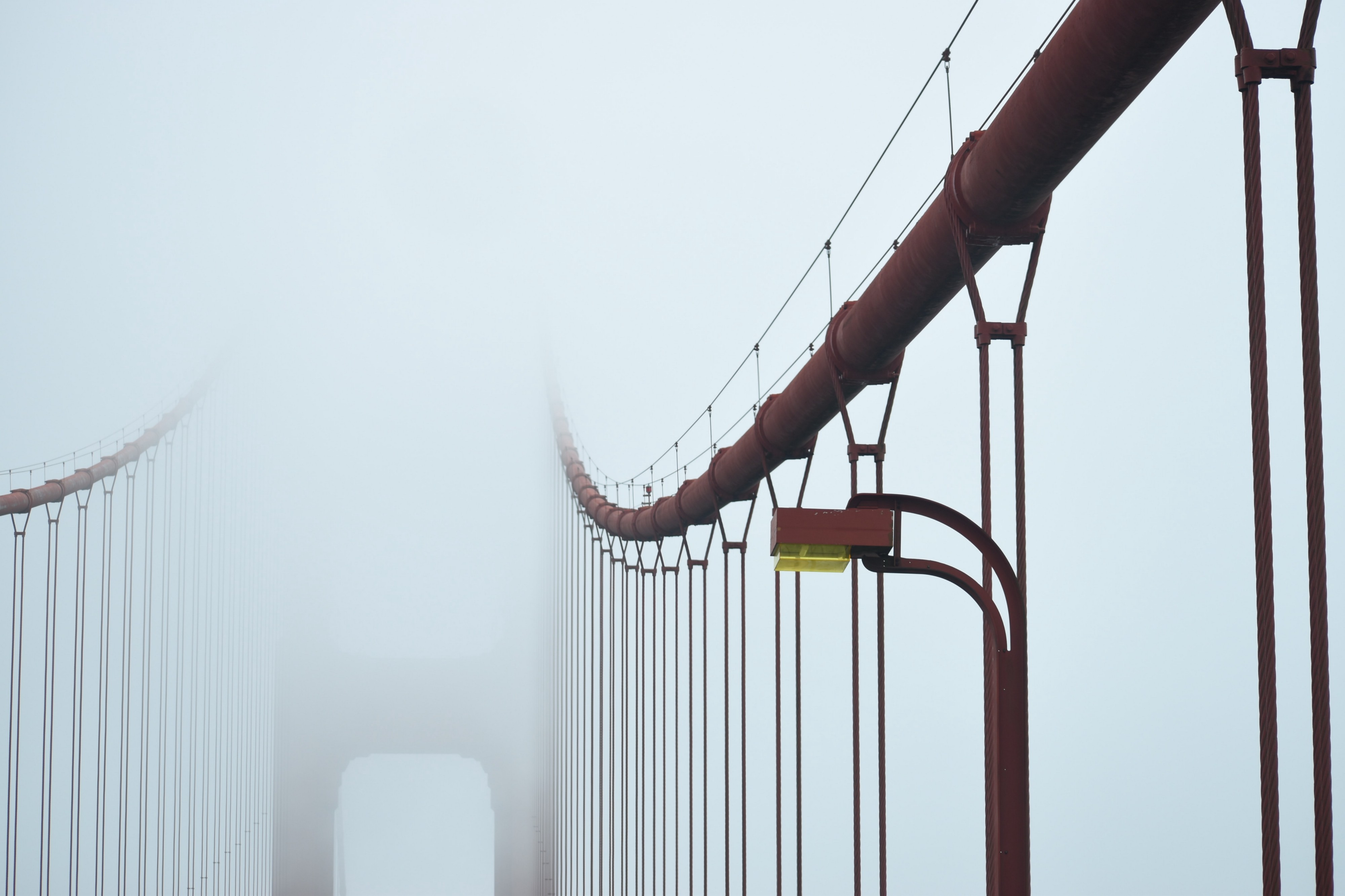 Fog covering red bridge, fading in the distance