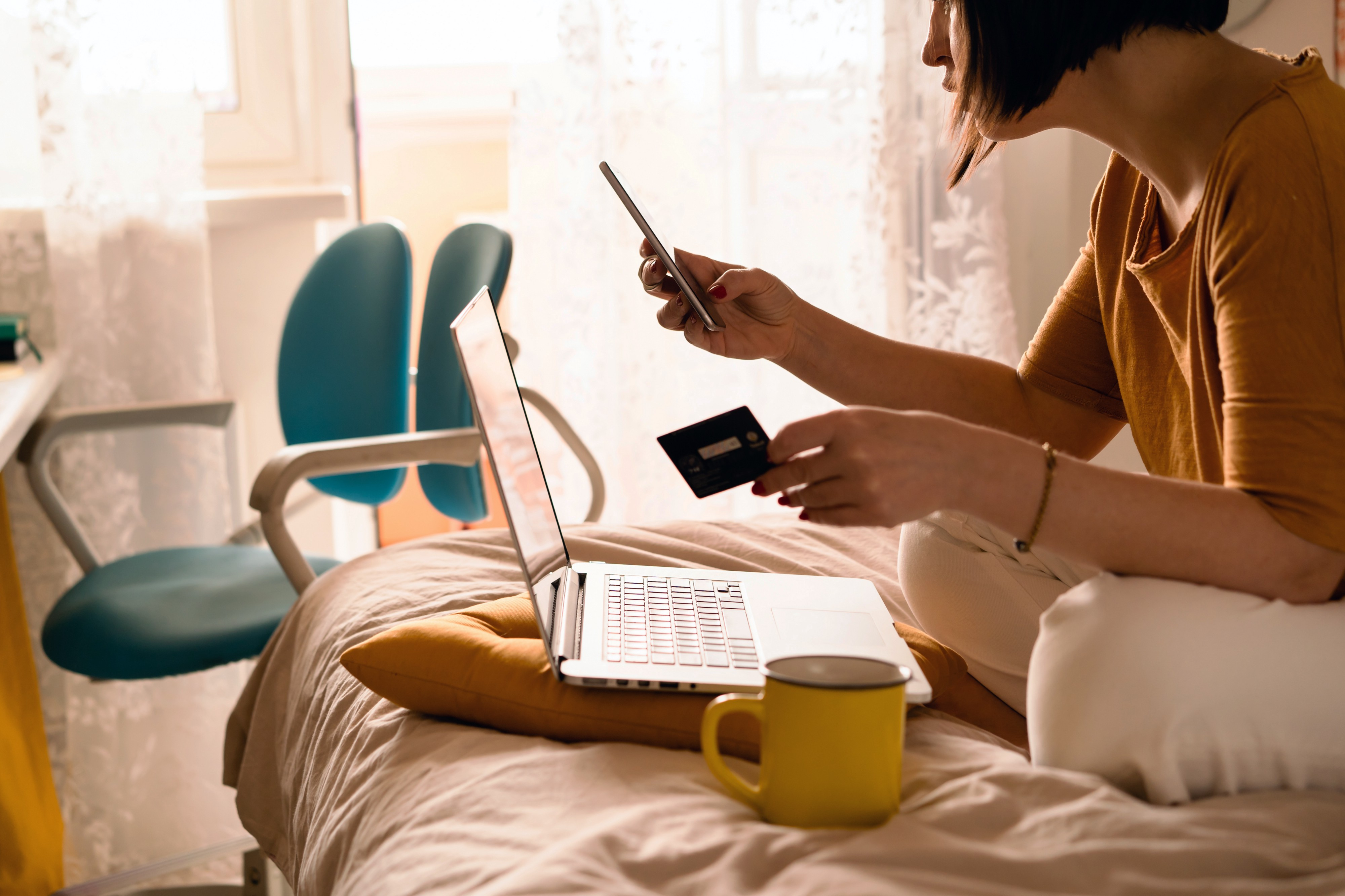 Woman holding credit card and looking at phone as she online shops.