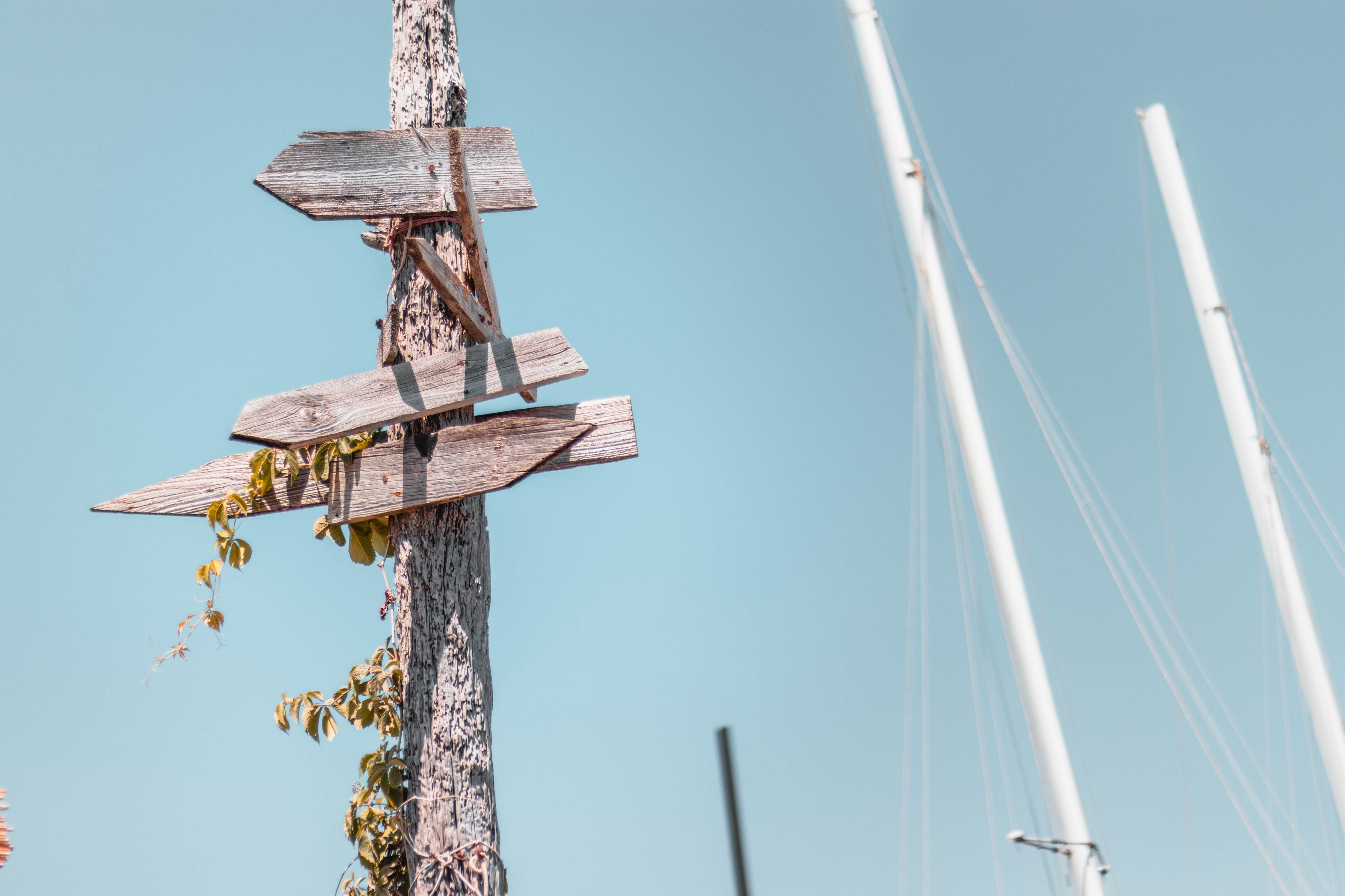 Wooden signpost with multiple directions being pointed to, although with no words on, against a pale blue sky.
