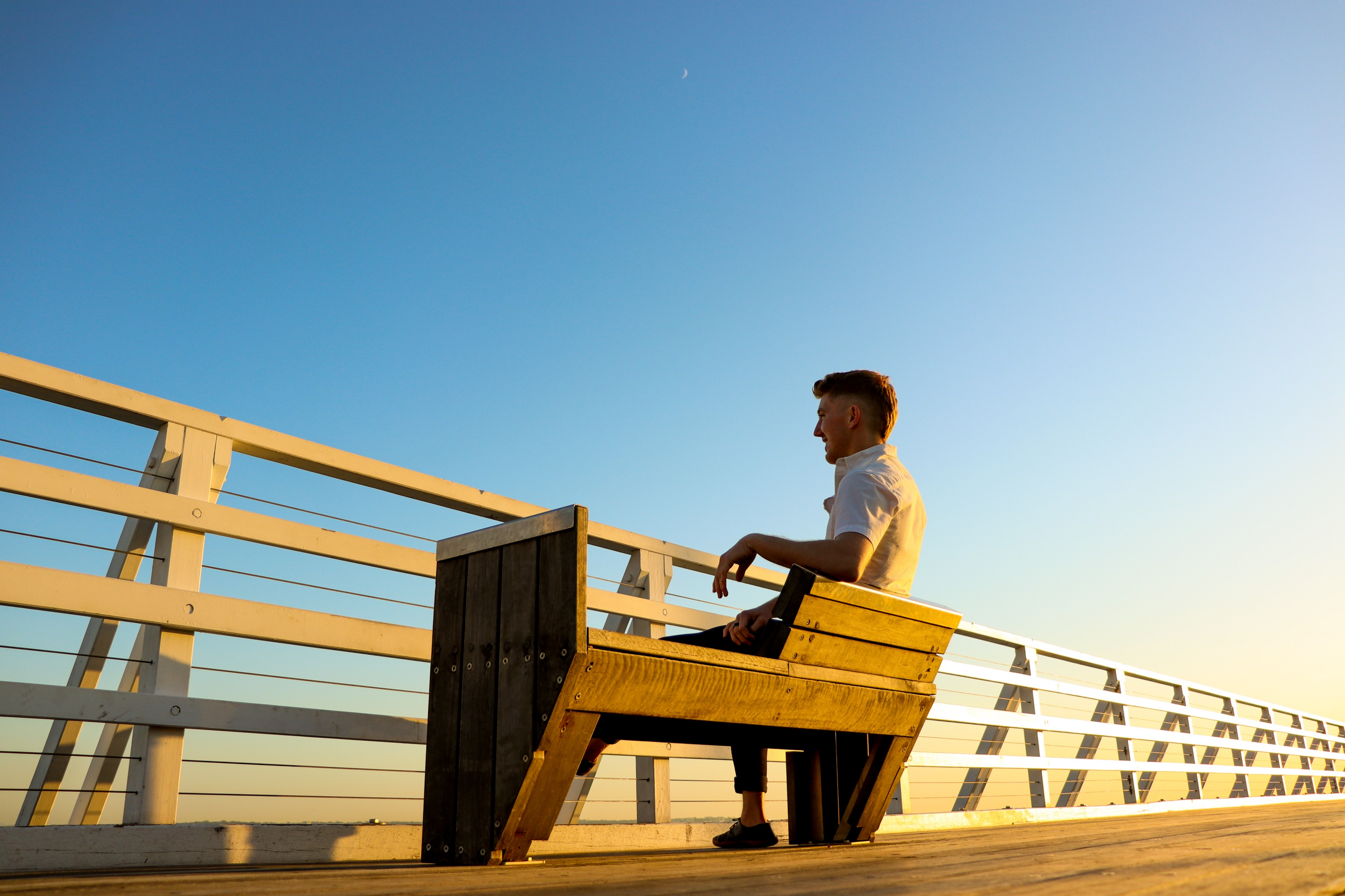 man sitting on a chair looking over the side of a wooden pier