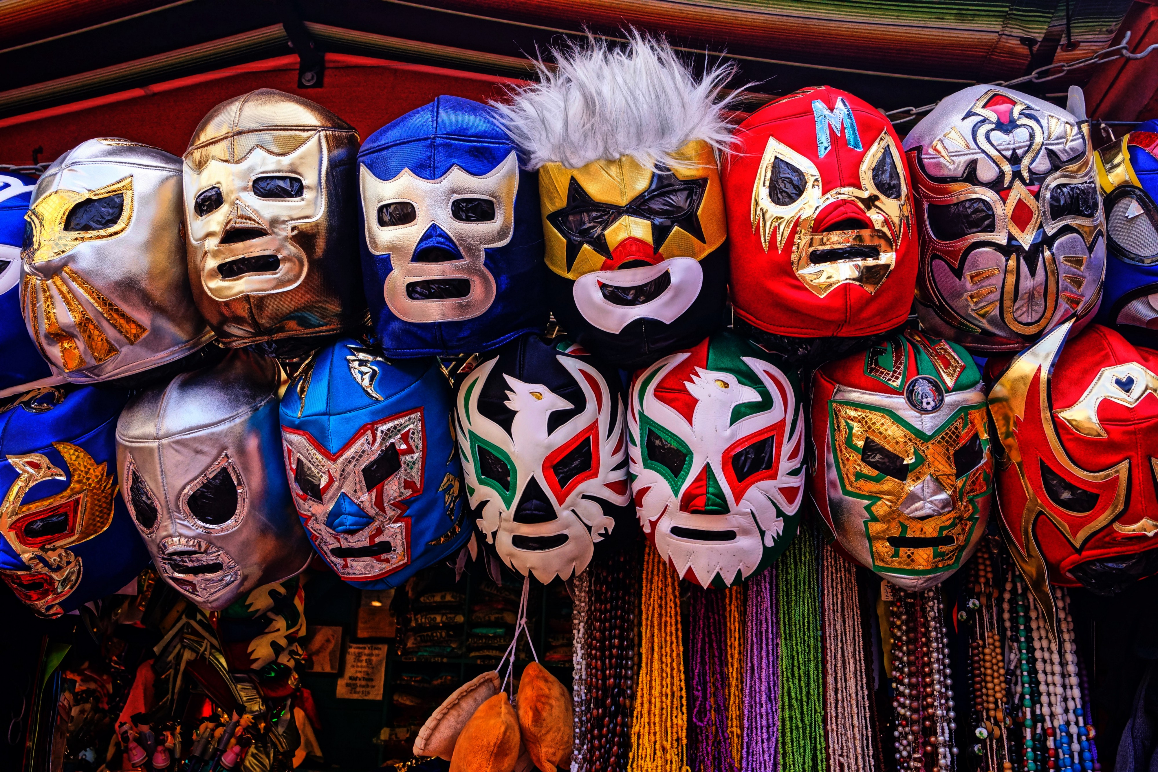 A booth in a mexican flea market that offers numerous different wrestling masks.