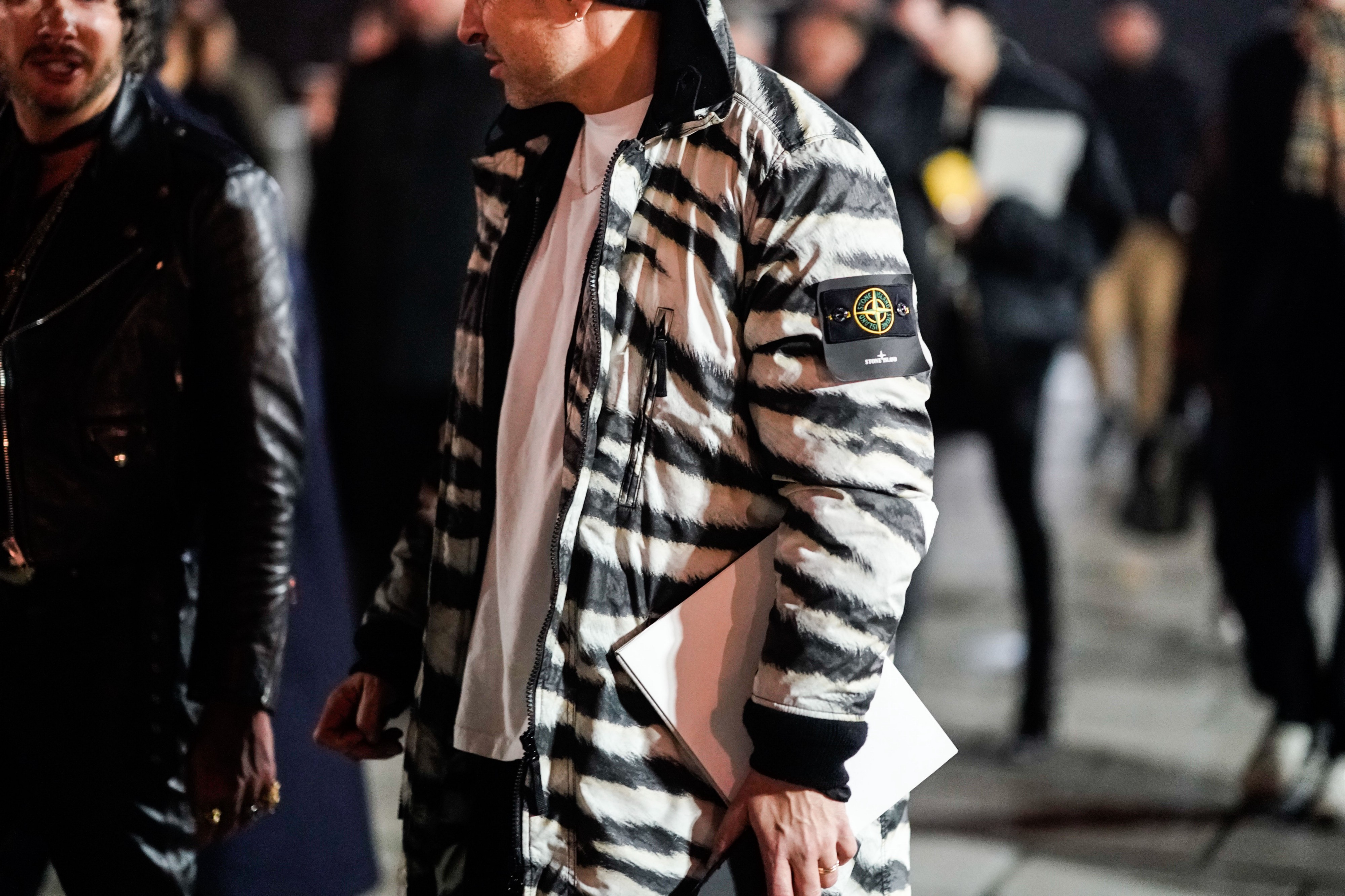"""A man wears a black and white zebra print bomber jacket from the brand """"Stone Island."""""""