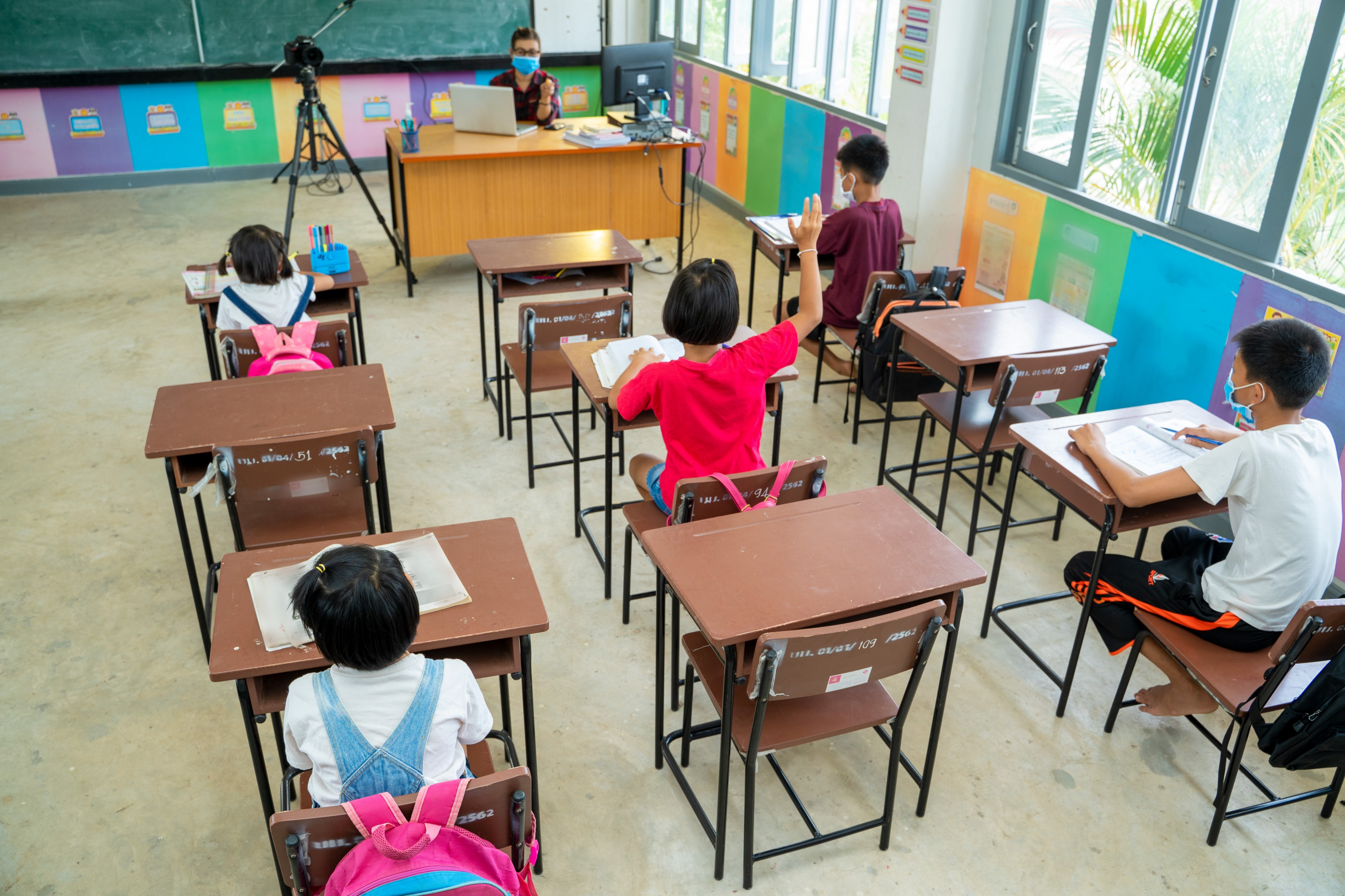 students separated by 6 ft social distancing in a class with a video camera at the front.