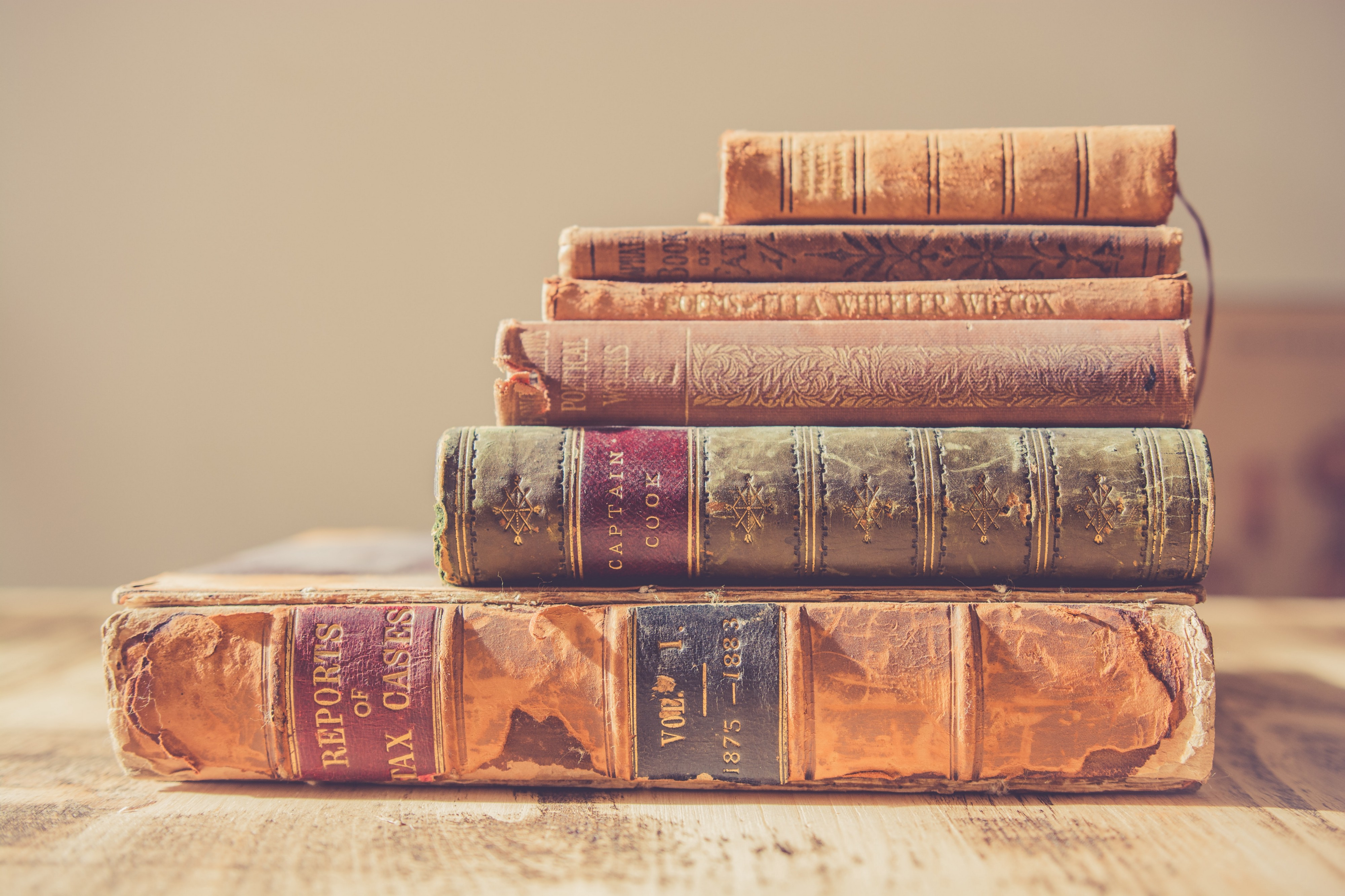 Five old books piled up top of one another