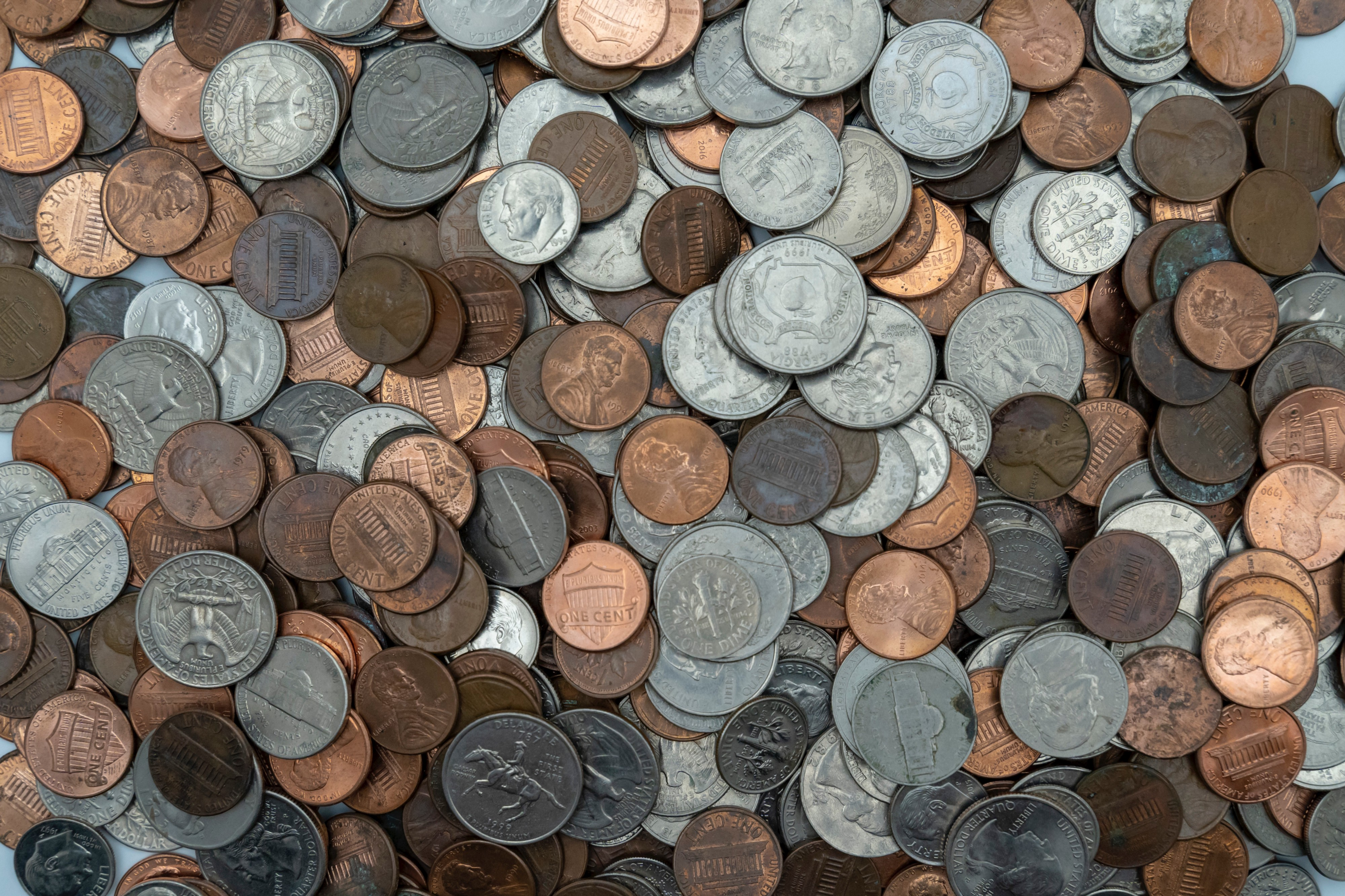 An assortment of coins spread out on a flat surface. Possibly a table.