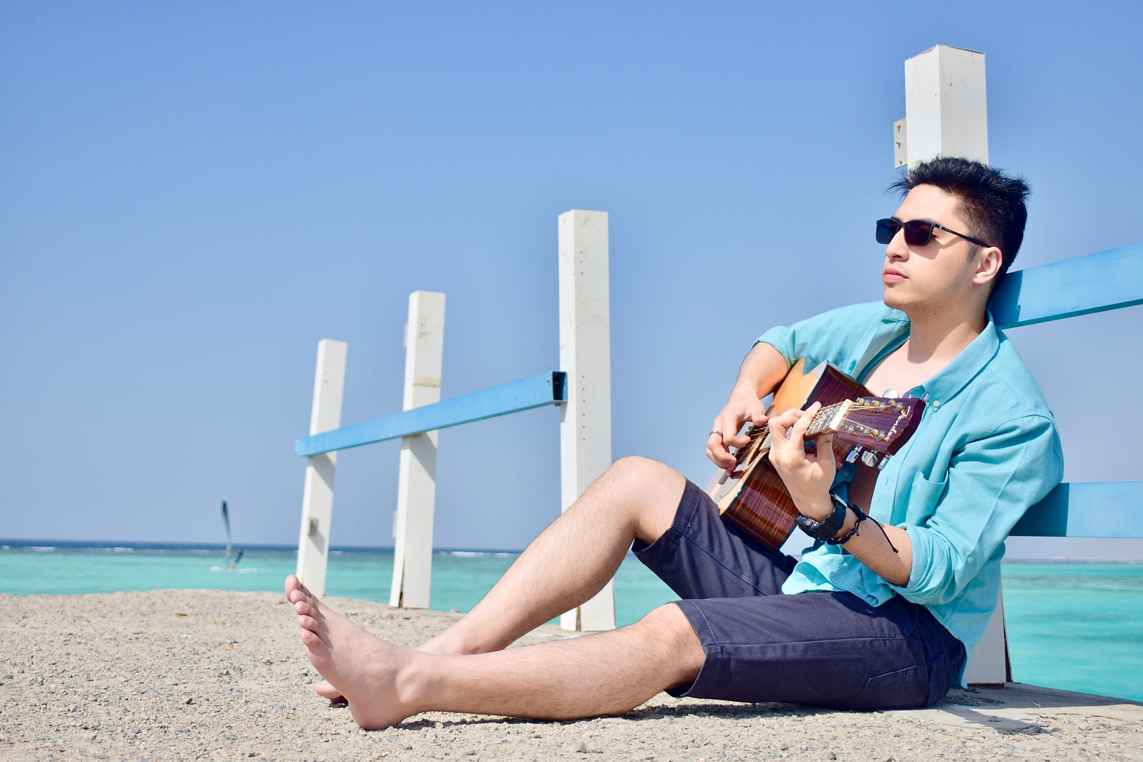 A man playing guitar in the pier during summer