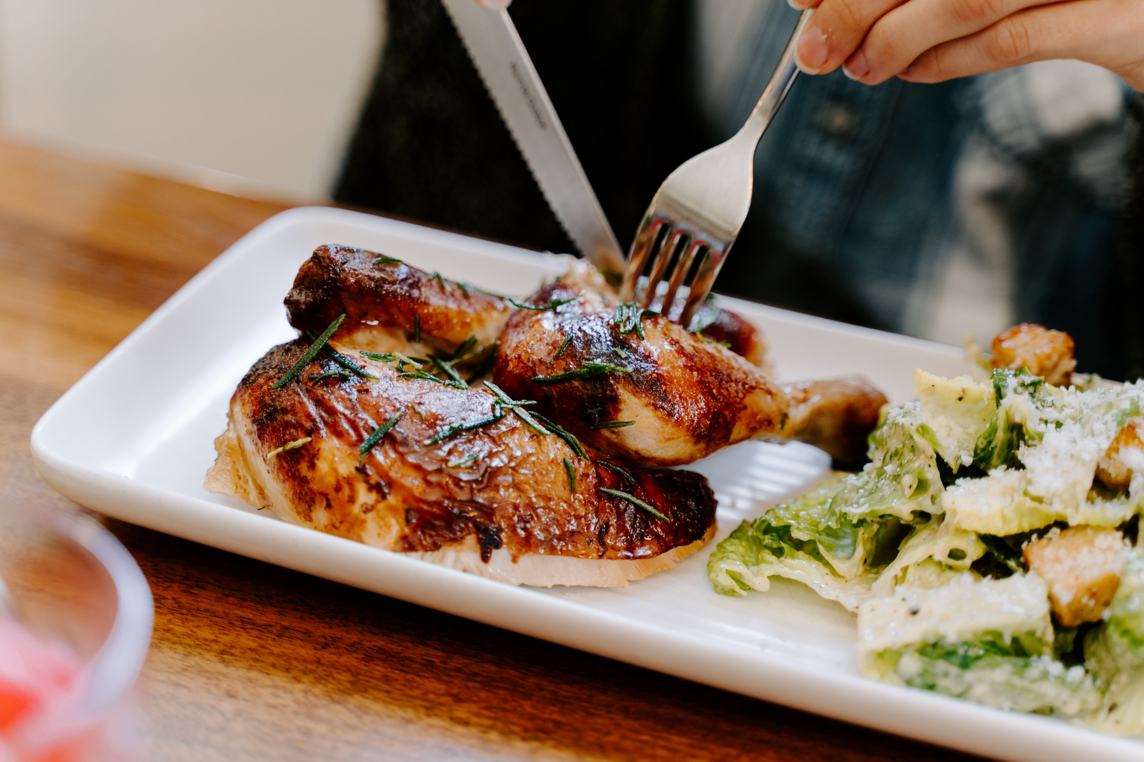 Roasted chicken on pate, being cut by knife and fork.