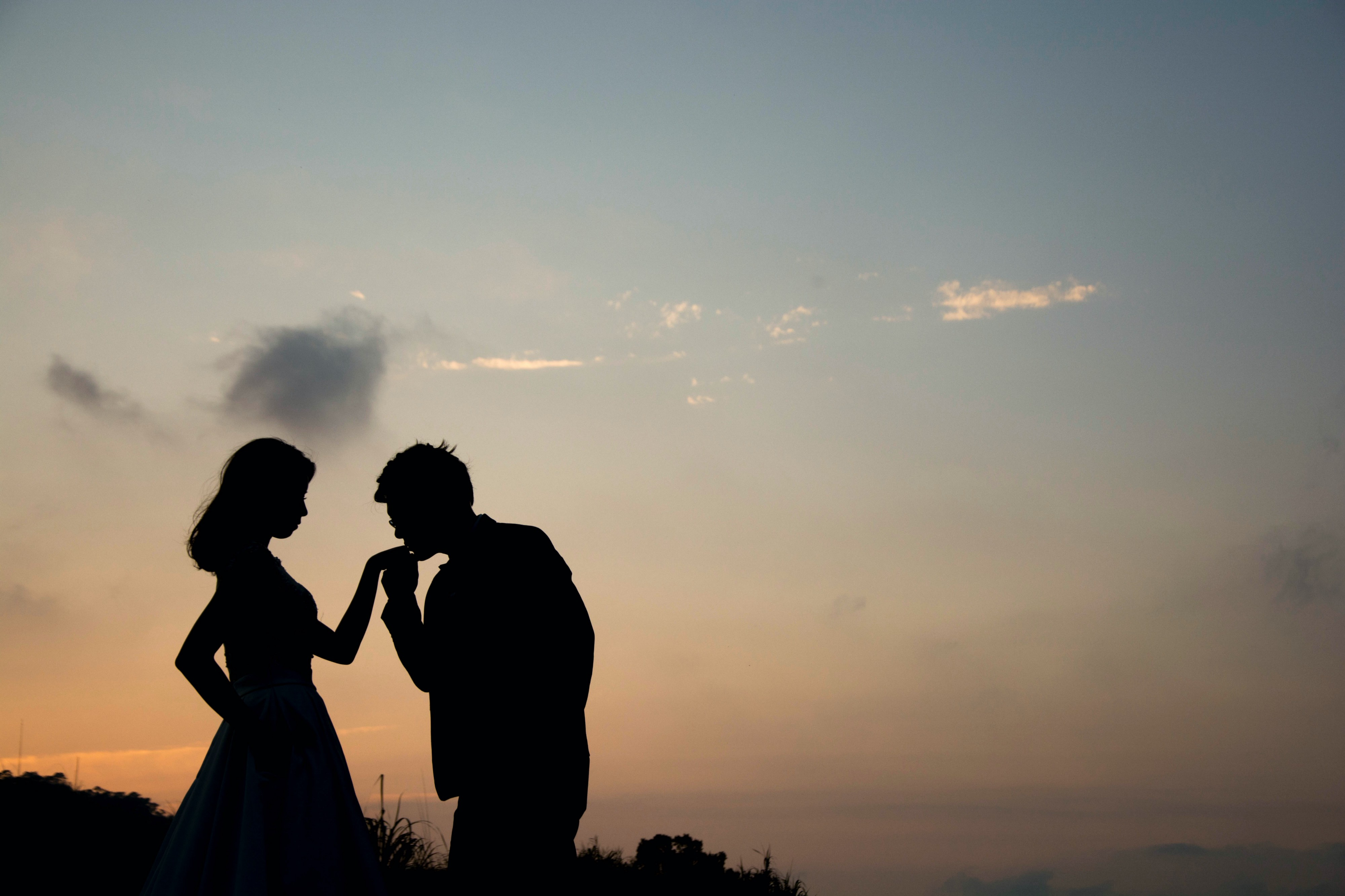 couple kissing in front of a sunset