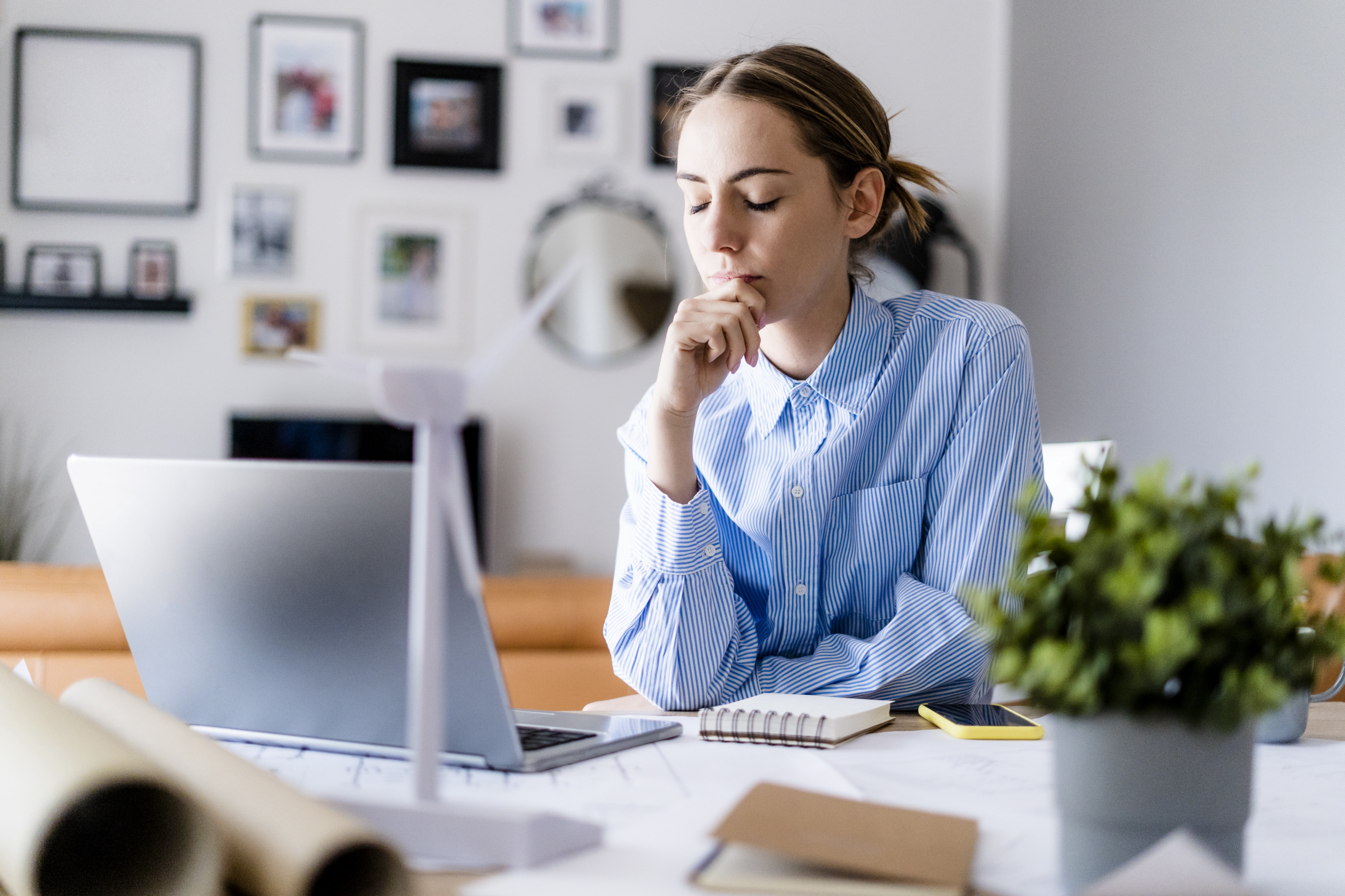 A woman closing her eyes in thought while sitting in front of her laptop at home.