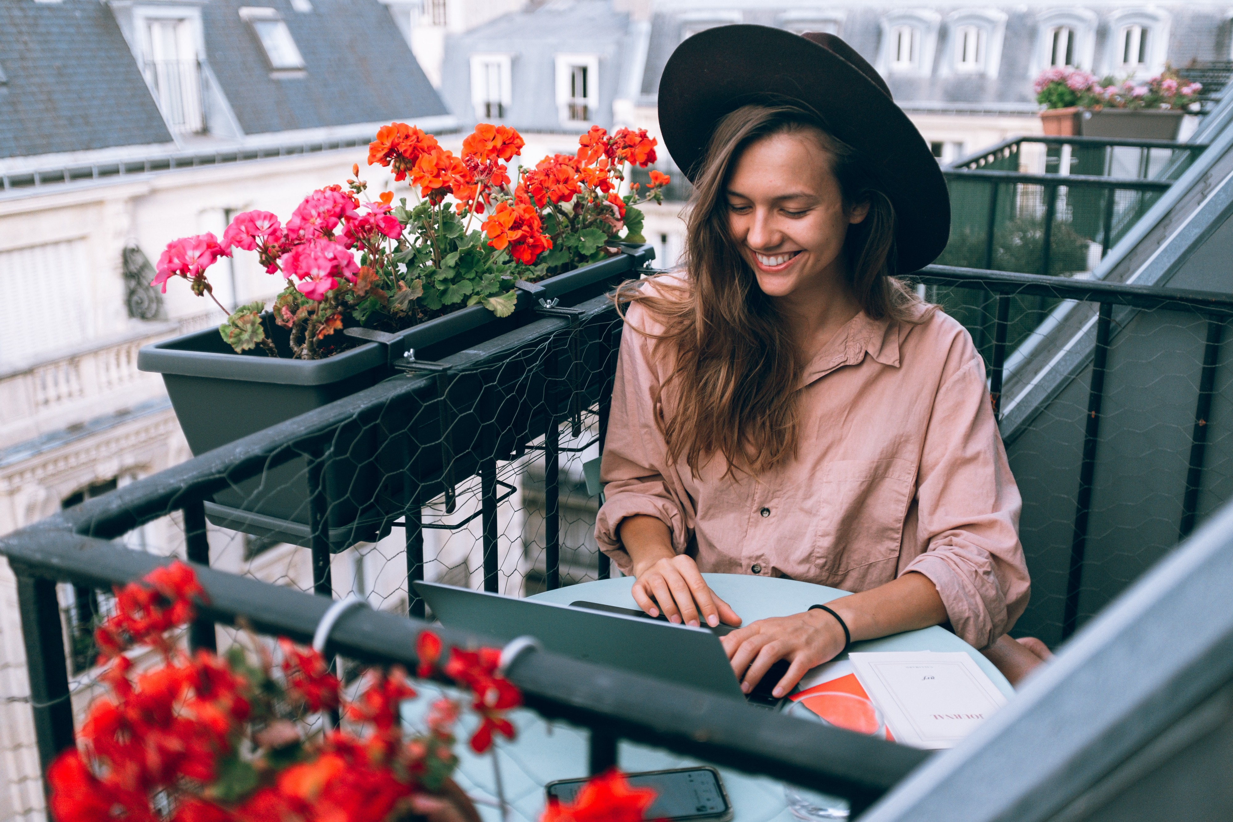 smiling woman sitting on a balcony writing on laptop and surrounded by flowers in window boxes