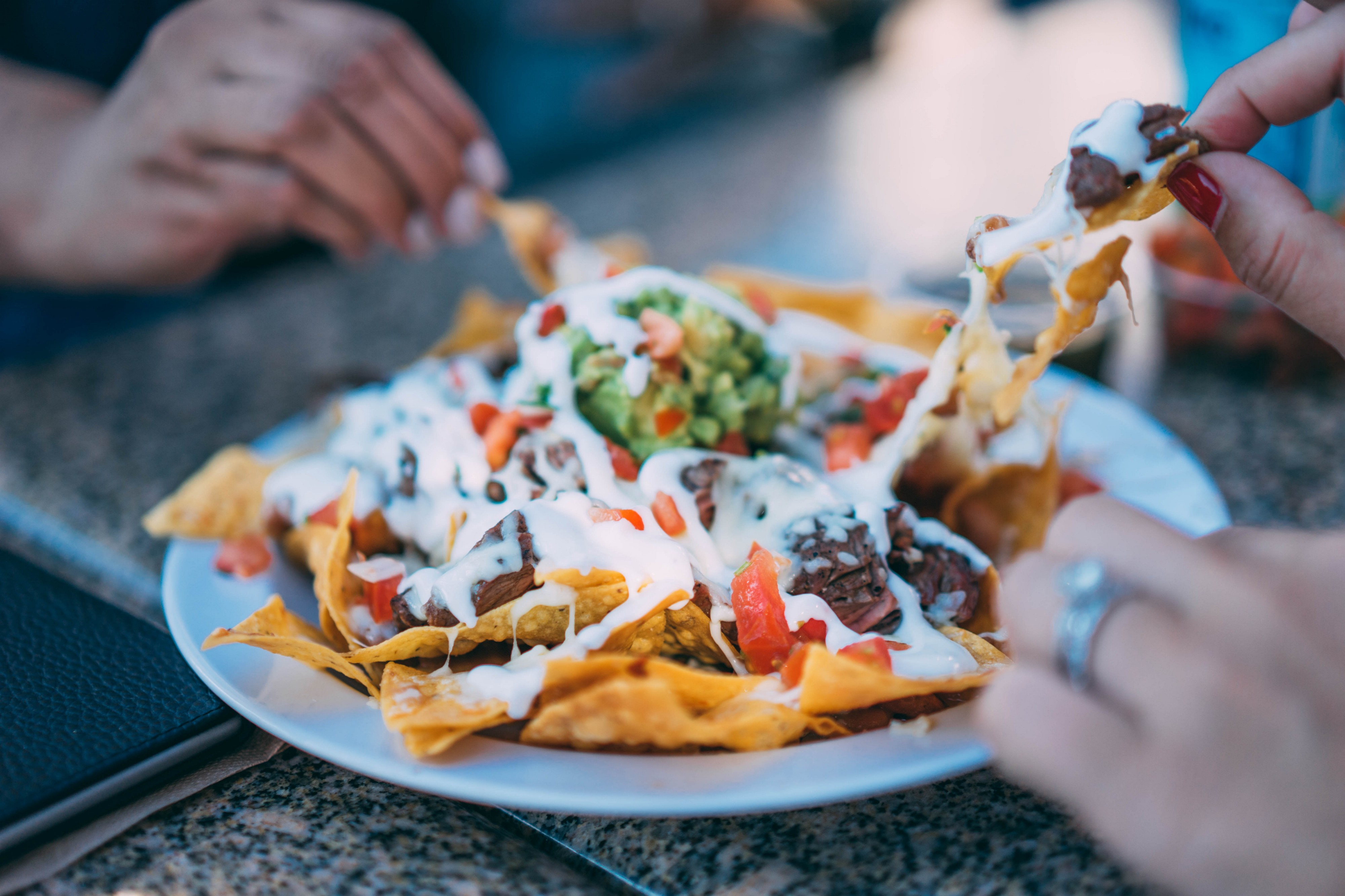 large plate of nachos being shared as an appetizer at a party