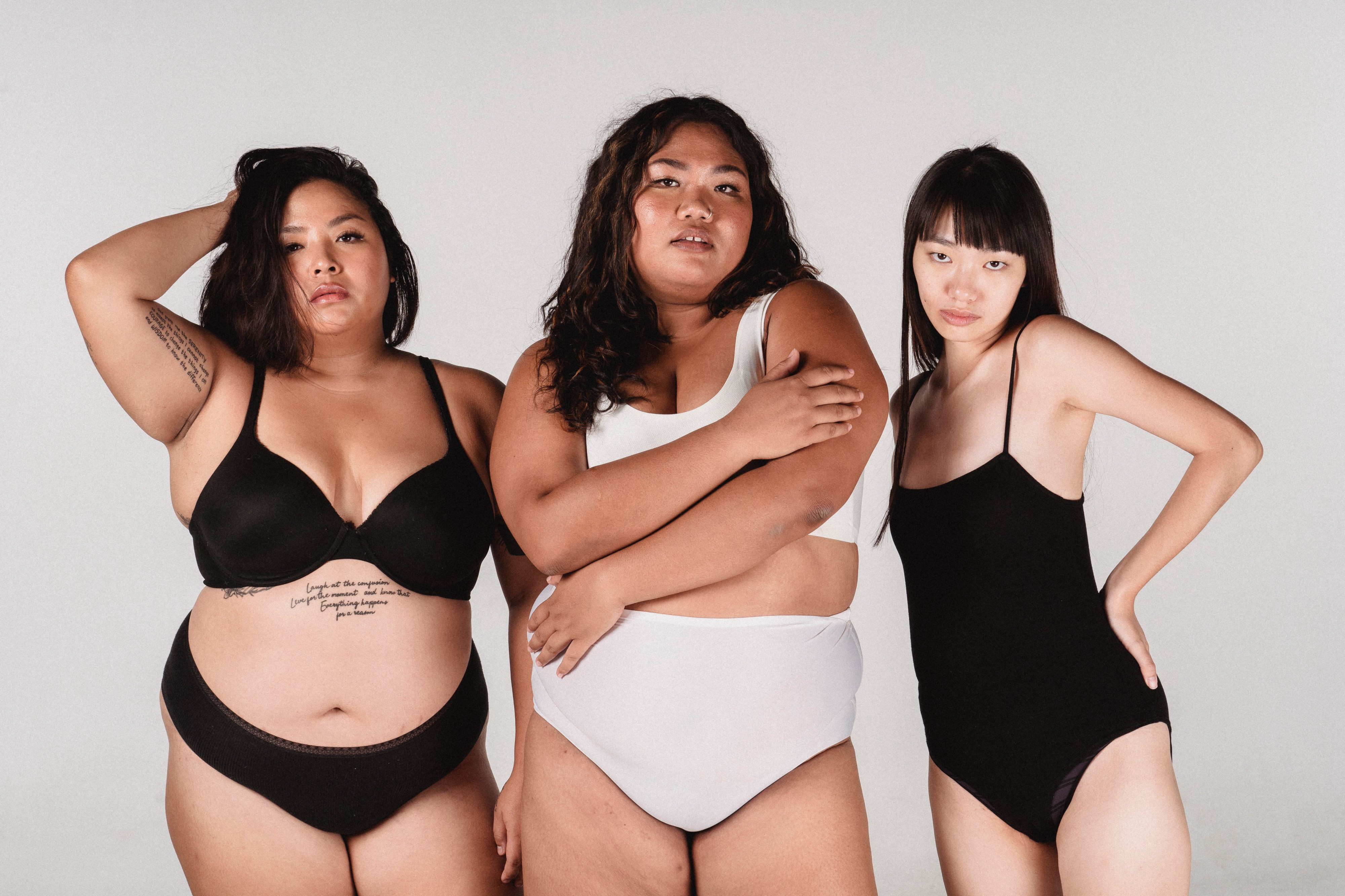 Three women standing together in their underwear. Two women are over-weight, while the last woman is very thin.