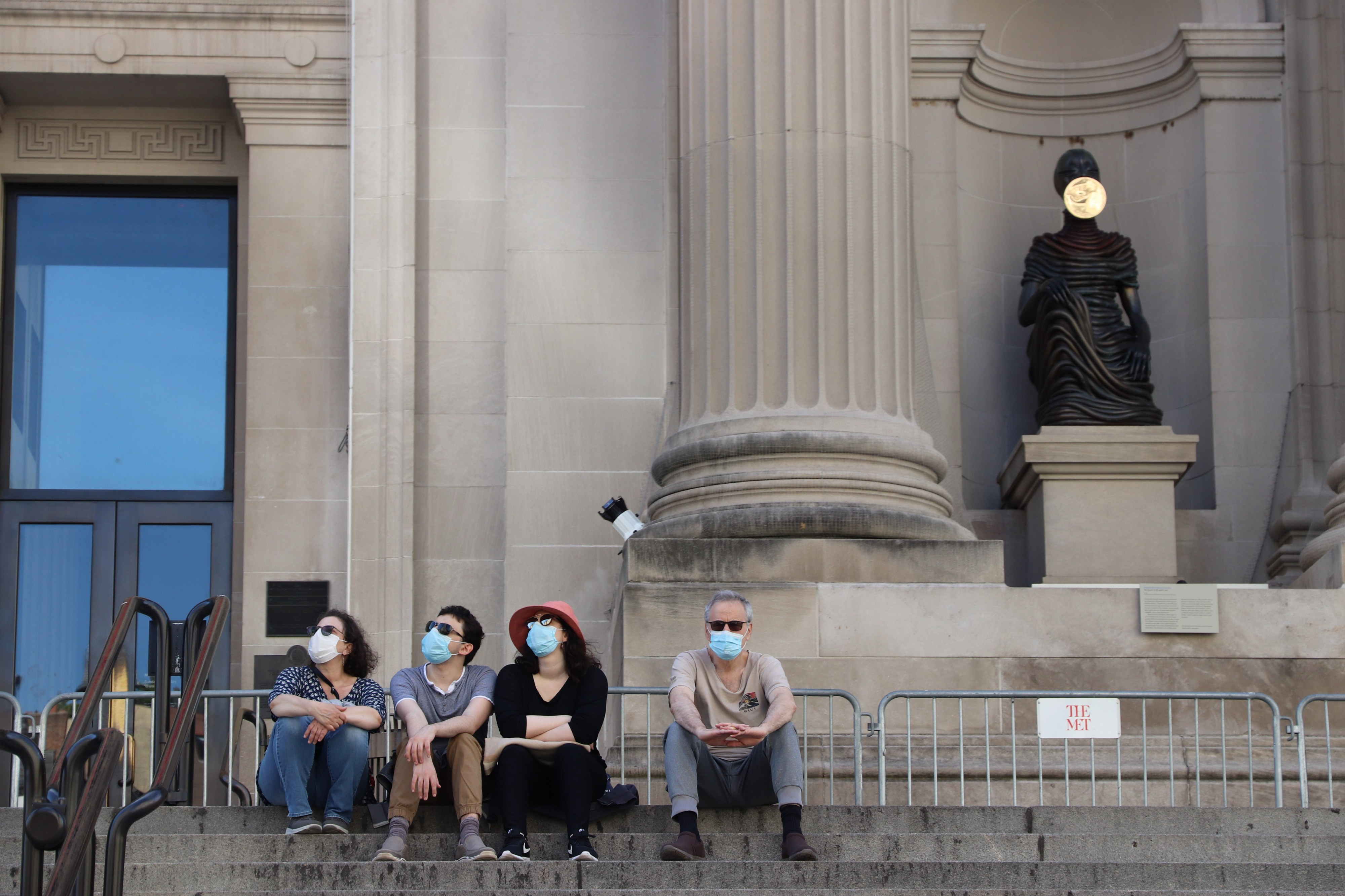 Visitors sit on the steps in front of the Metropolitan Museum of Art, closed because of the coronavirus