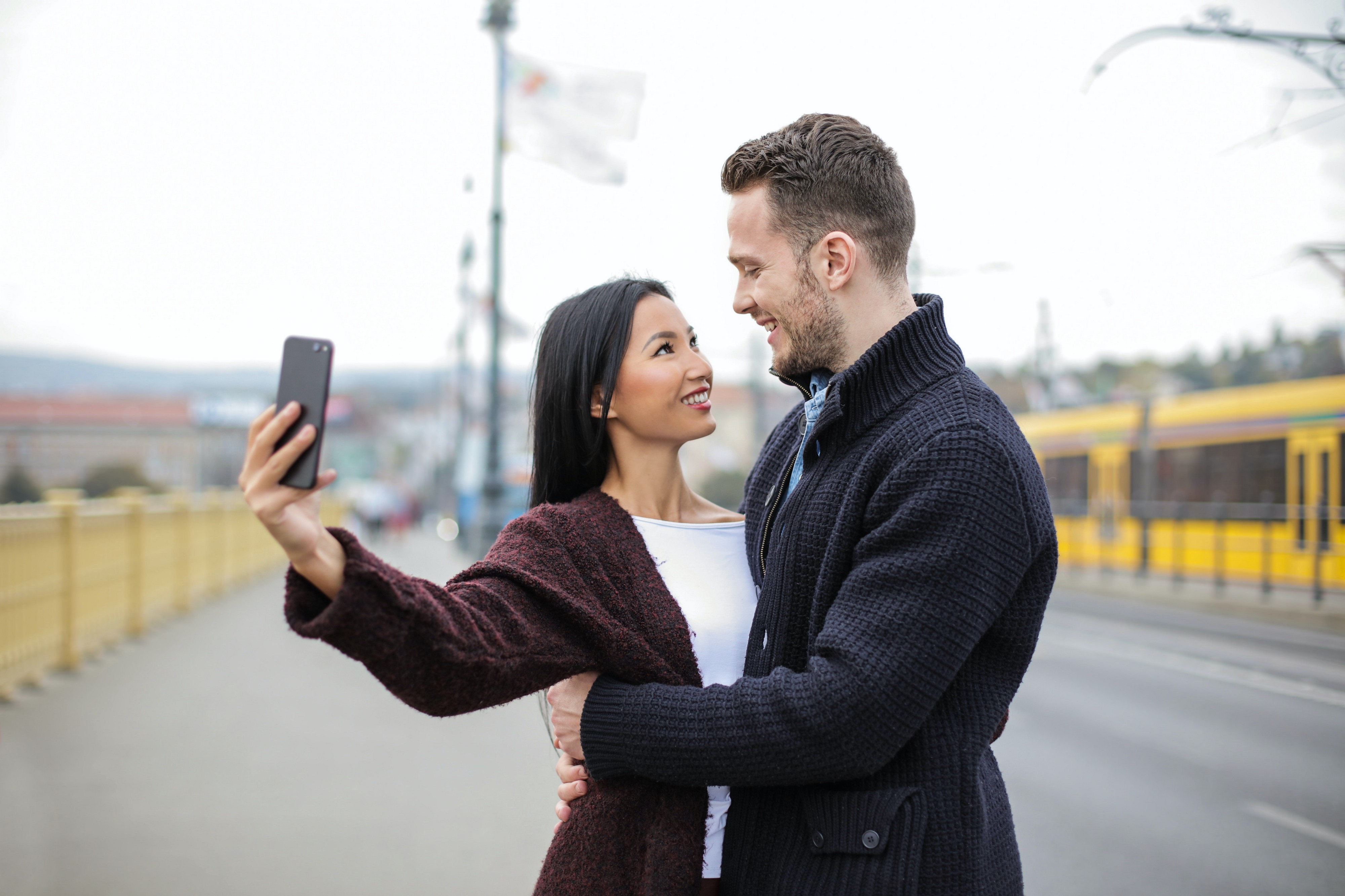 Woman holding phone, taking selfie with man