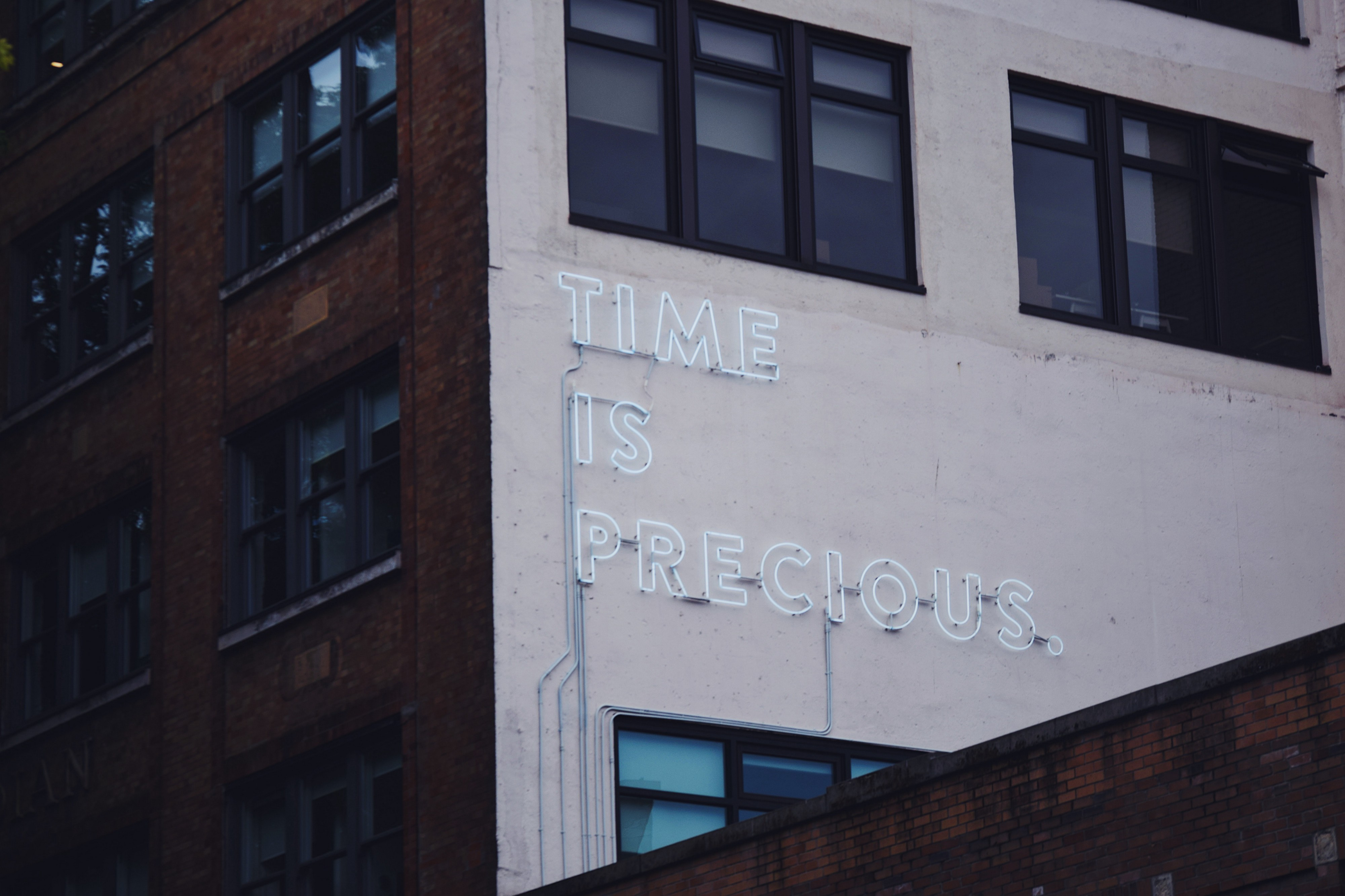 """Neon sign on a side of a building, """"time is precious"""""""