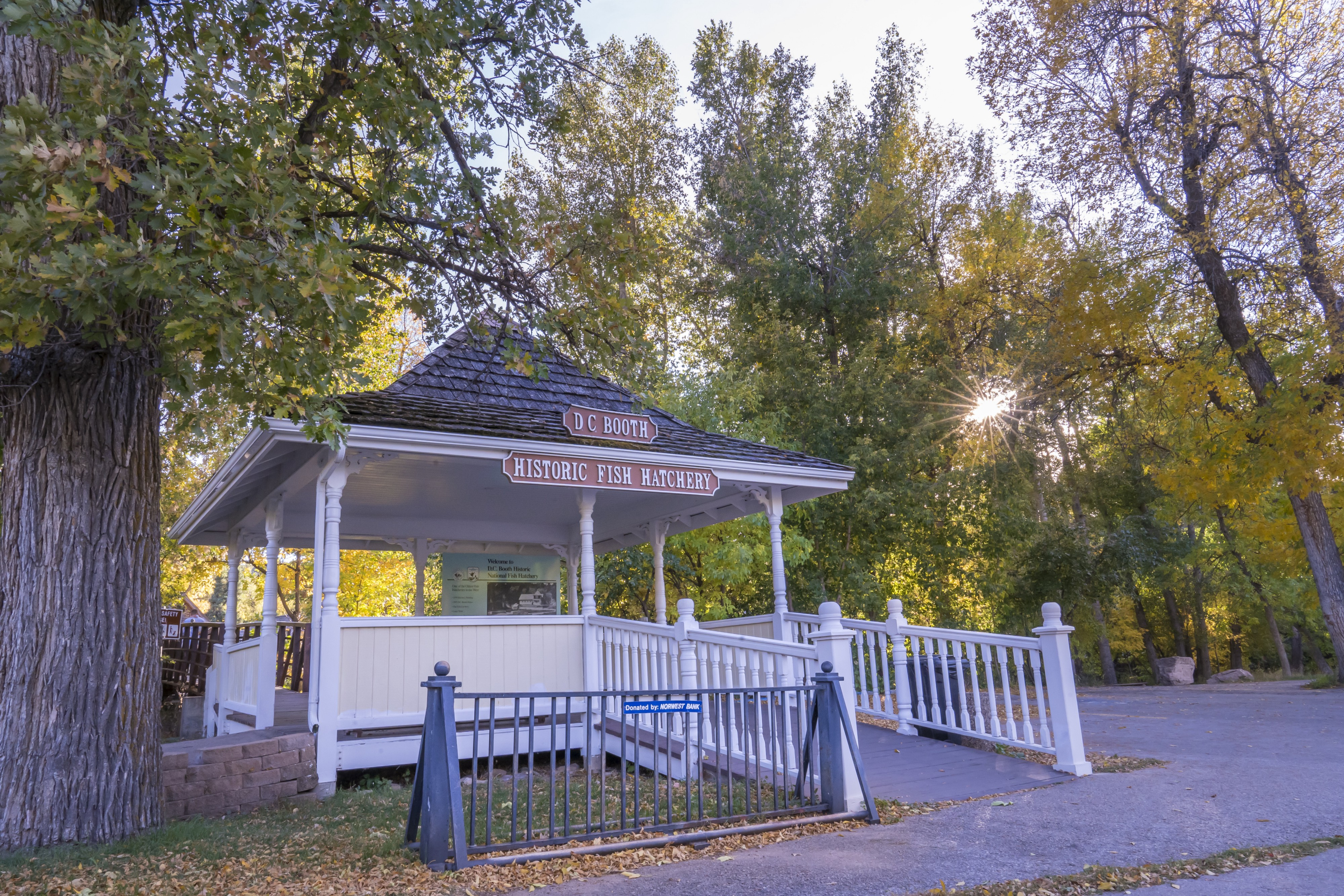 """A white gazebo with a sign that says """"Historic Fish Hatchery."""" Trees with green and gold leaves are in the background."""
