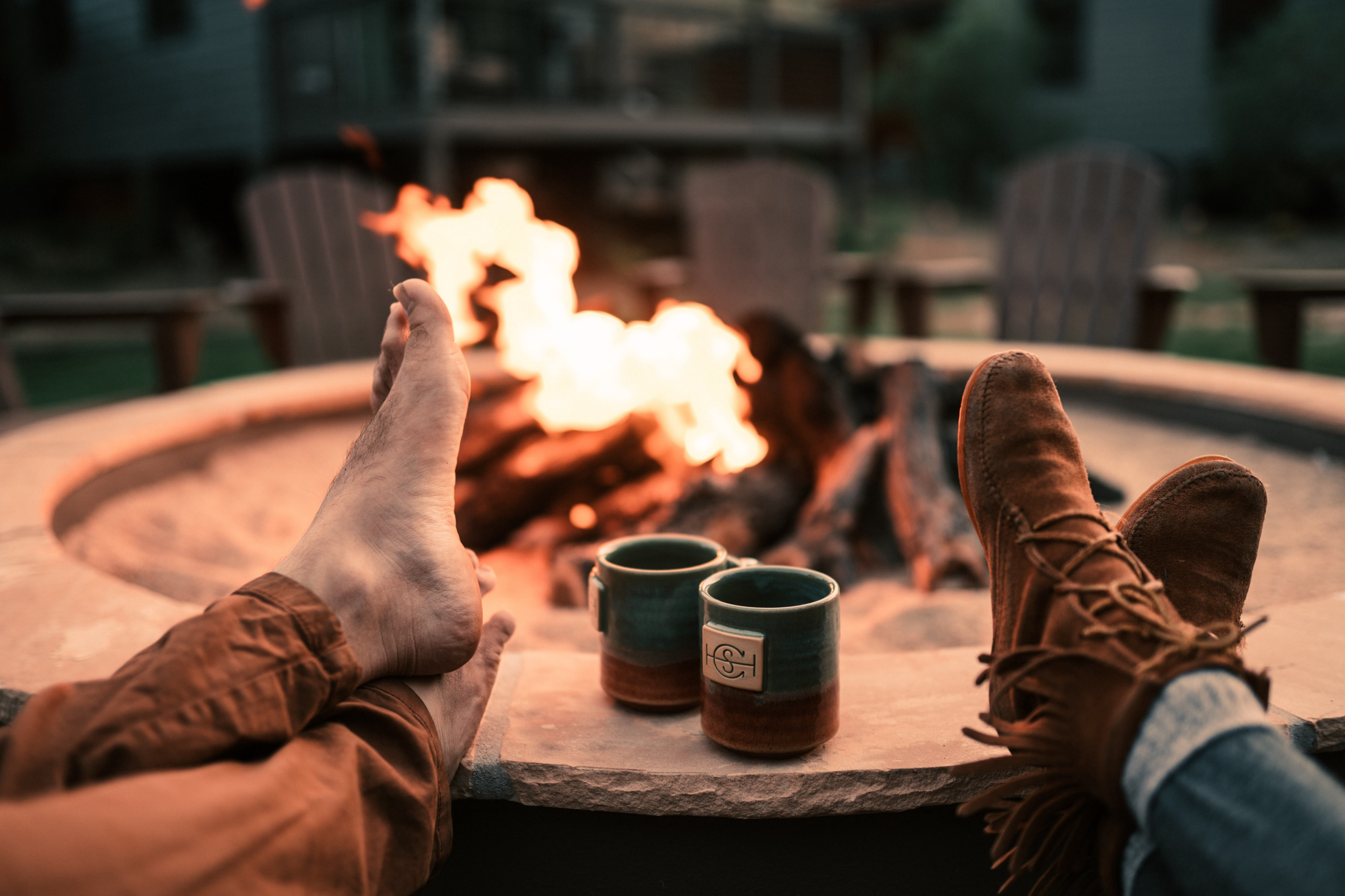 Two sets of feet rest on the edge of a large fire pit. Mugs sit between the feet. A fire burns in the background.
