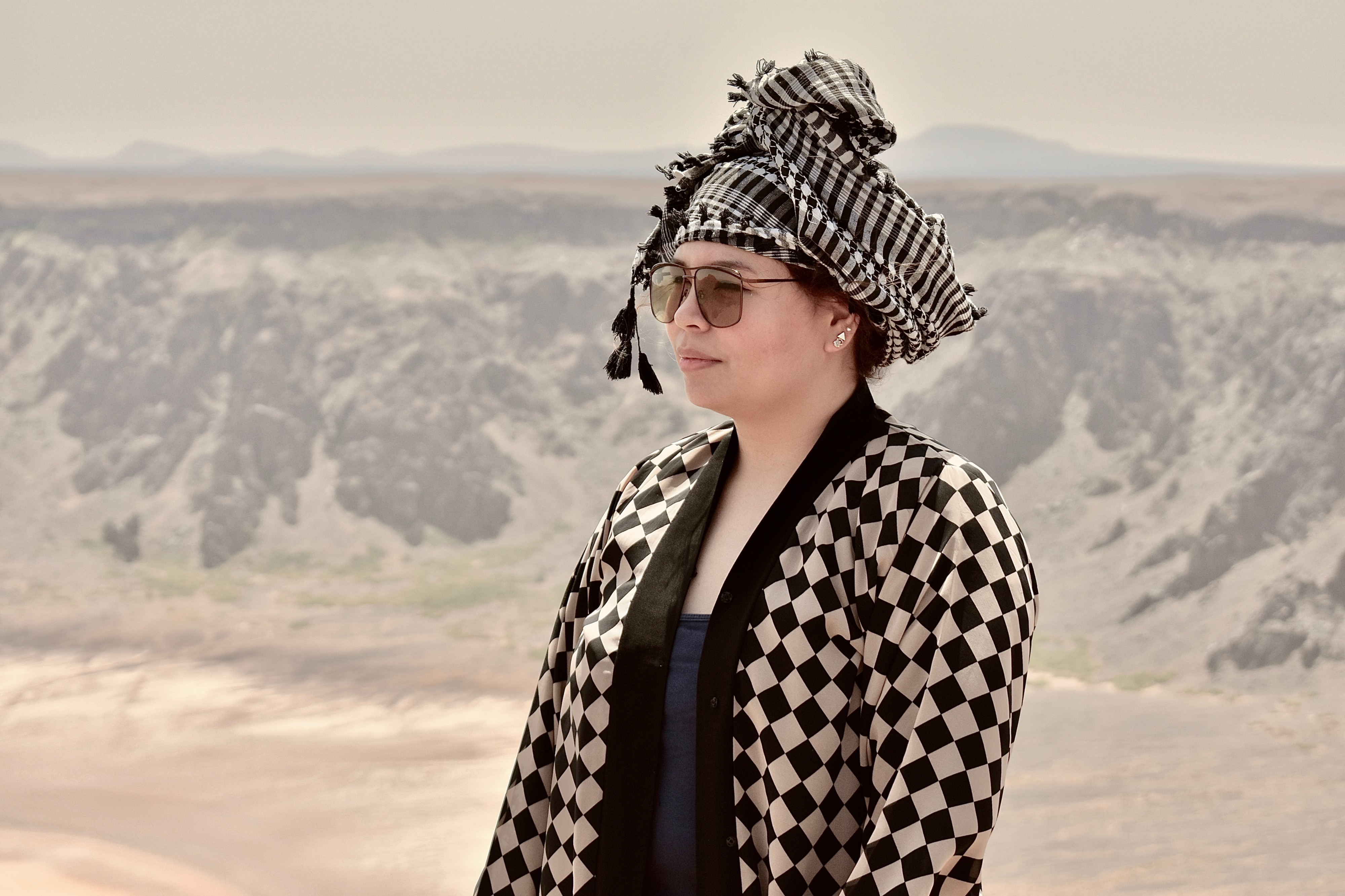 A beautiful tourist standing at the top of a passive volcanic crater in Saudi Arabia