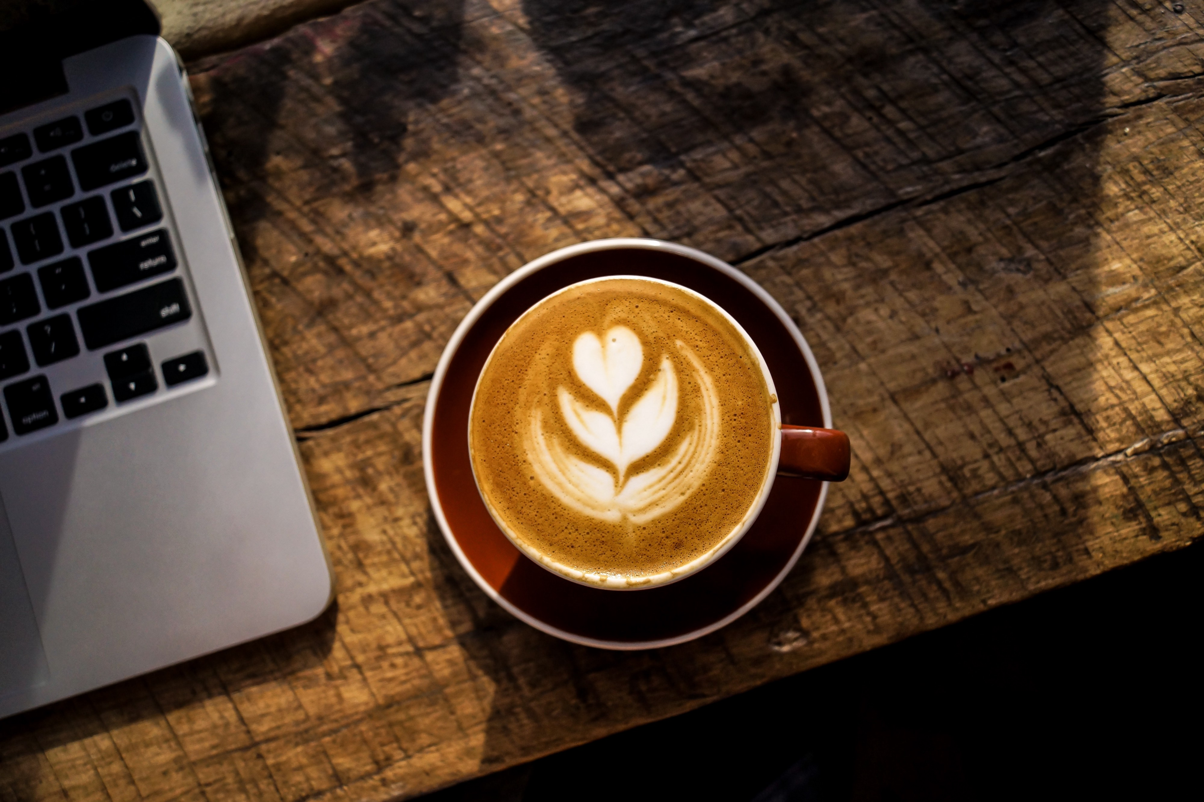 A cup of coffee with a beautiful latte art on the table next to a laptop.