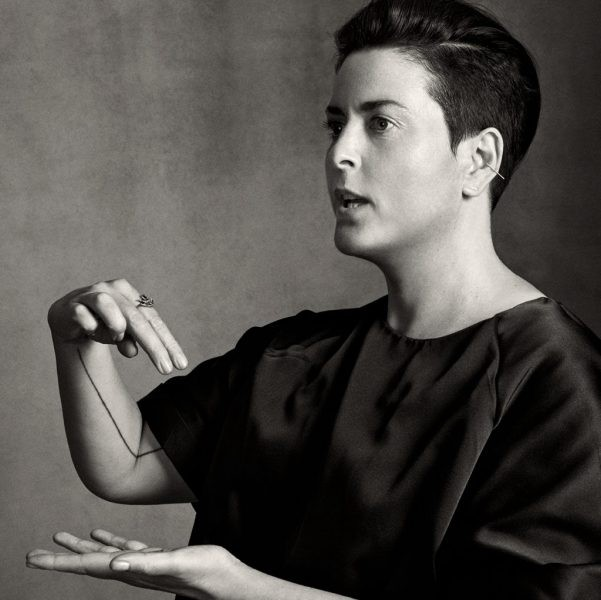 A black-and-white portrait of Charlotte Cotton speaking and gesturing.