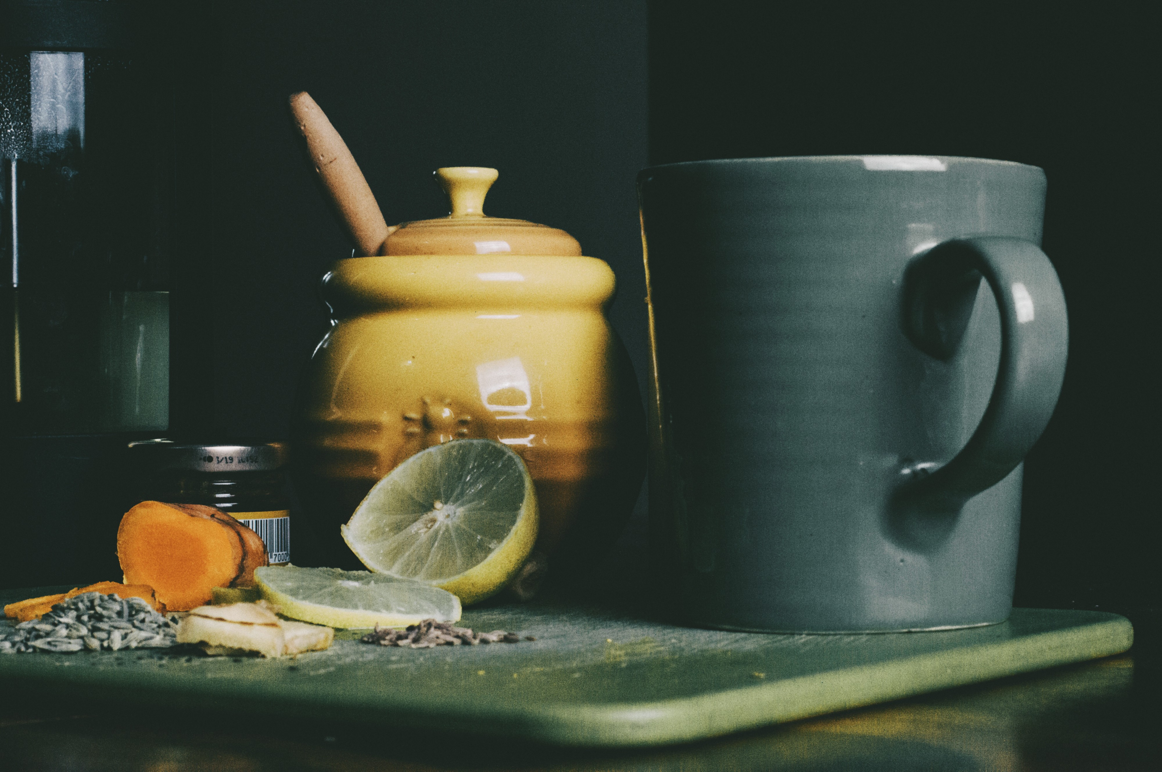 A cup with a cut lemon and honey pot beside of it.