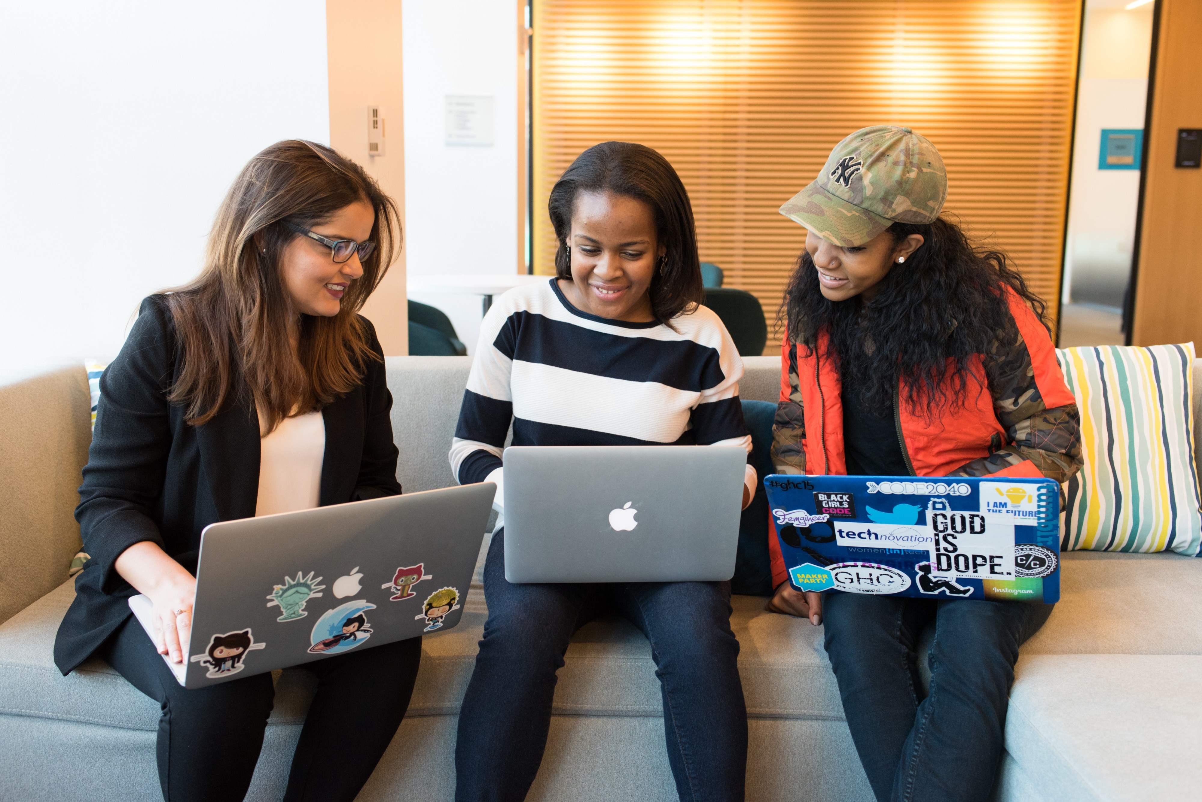 Three young women sit around a couch looking at their laptops.
