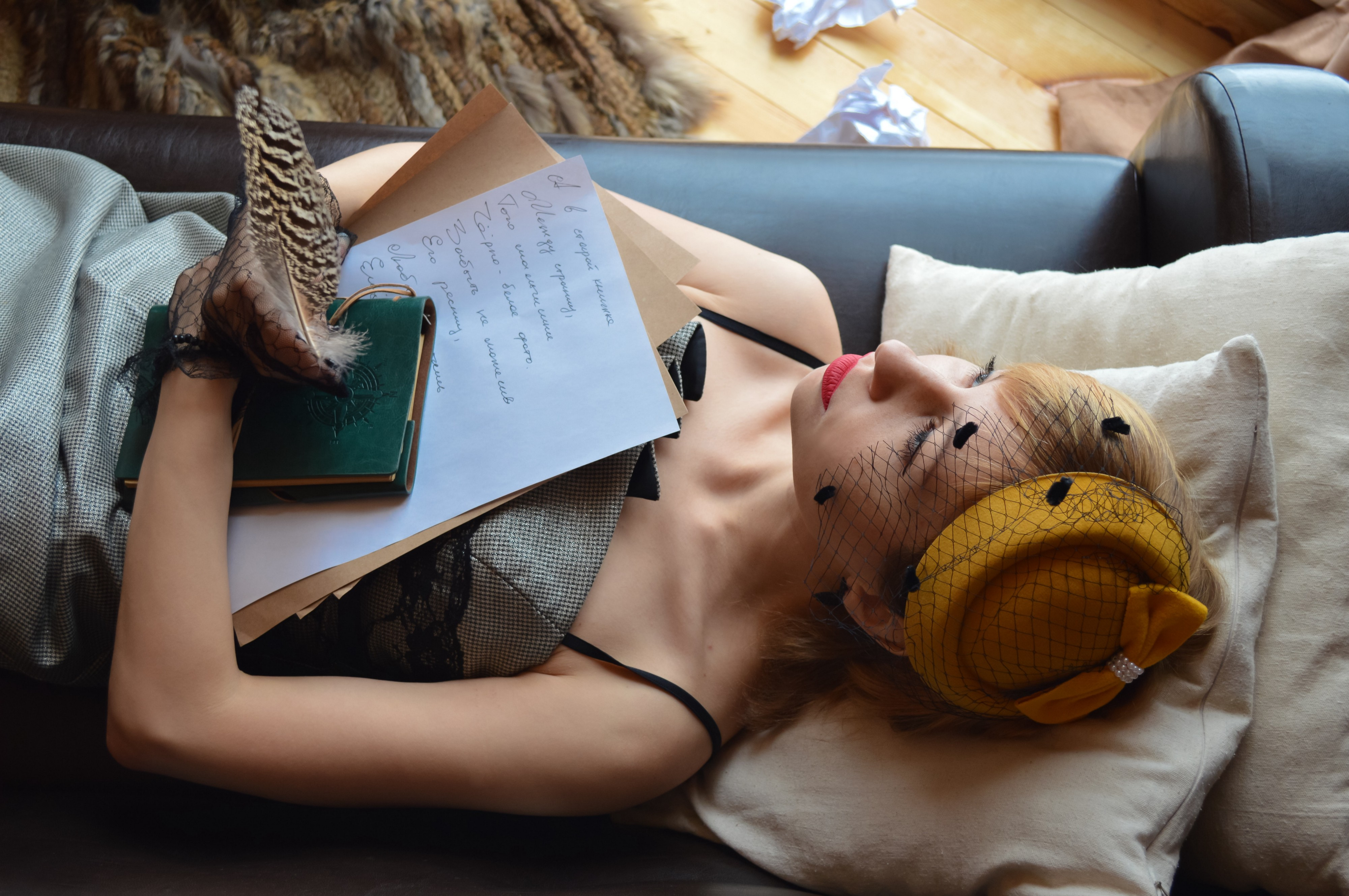 Elegant woman dressed in vintage attire, laying on a couch. She is holding papers, a notebook, and a feathered pen. Crumpled papers lay on the wooden floor behind the couch.