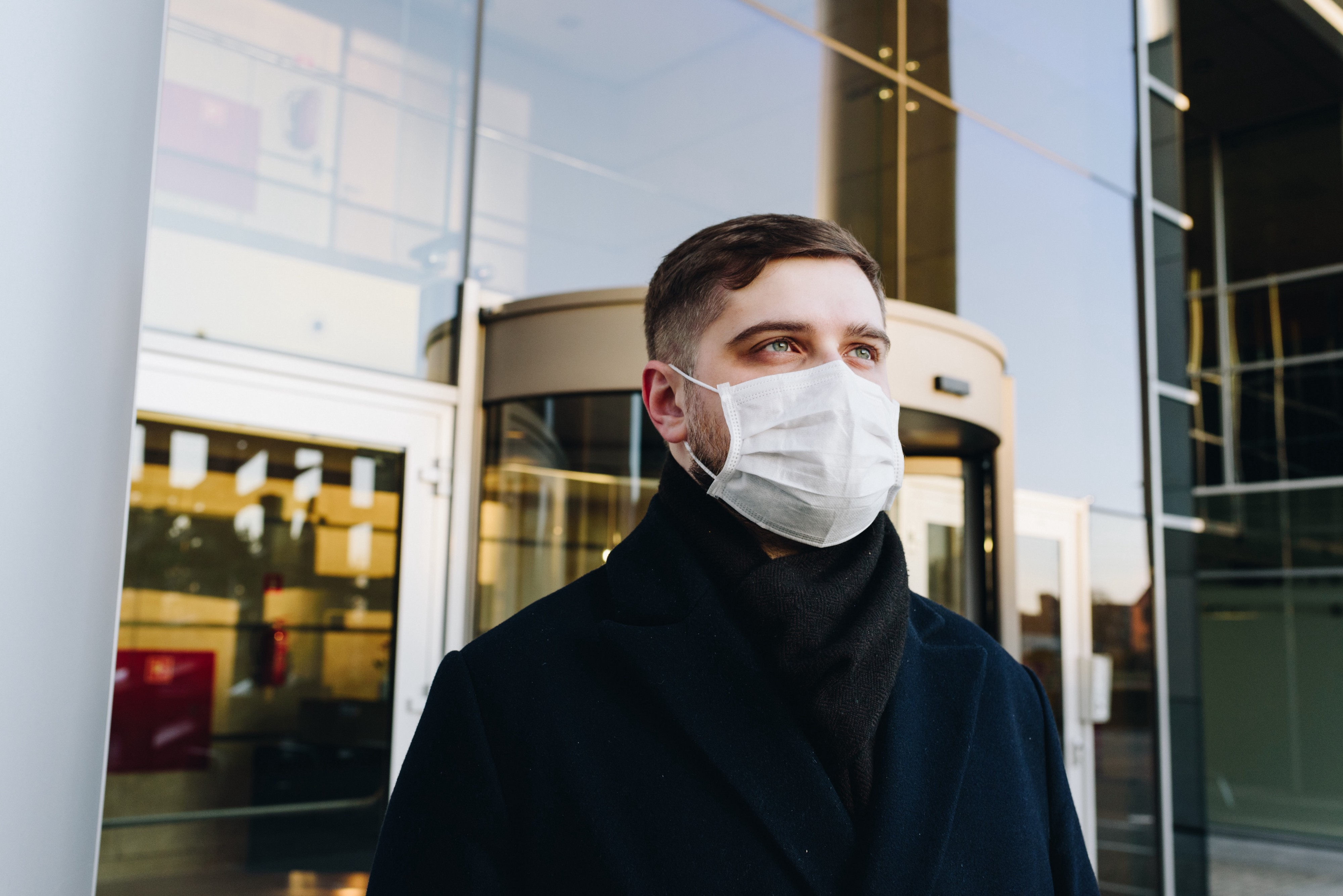 Blue-collar men wearing a face mask looking towards the sky during the coronavirus crisis