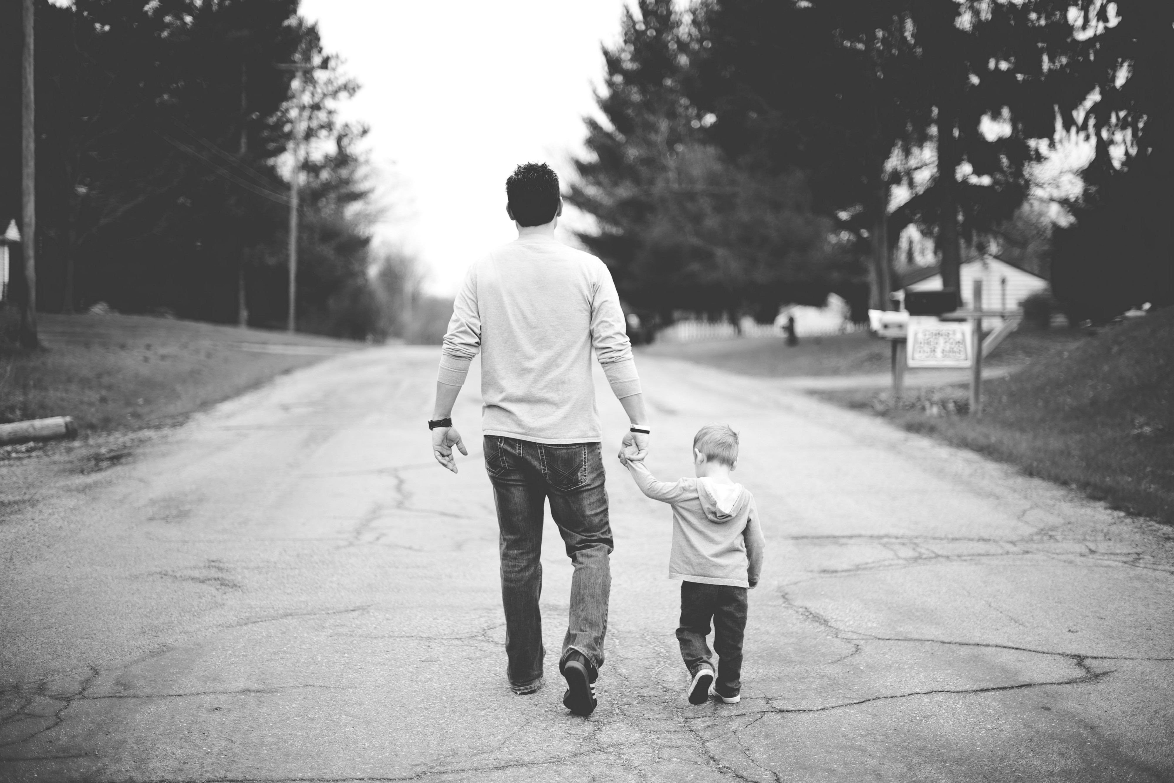 black and white photos of man wearing white shirt holding hands with little boy walking along road in neighborhood
