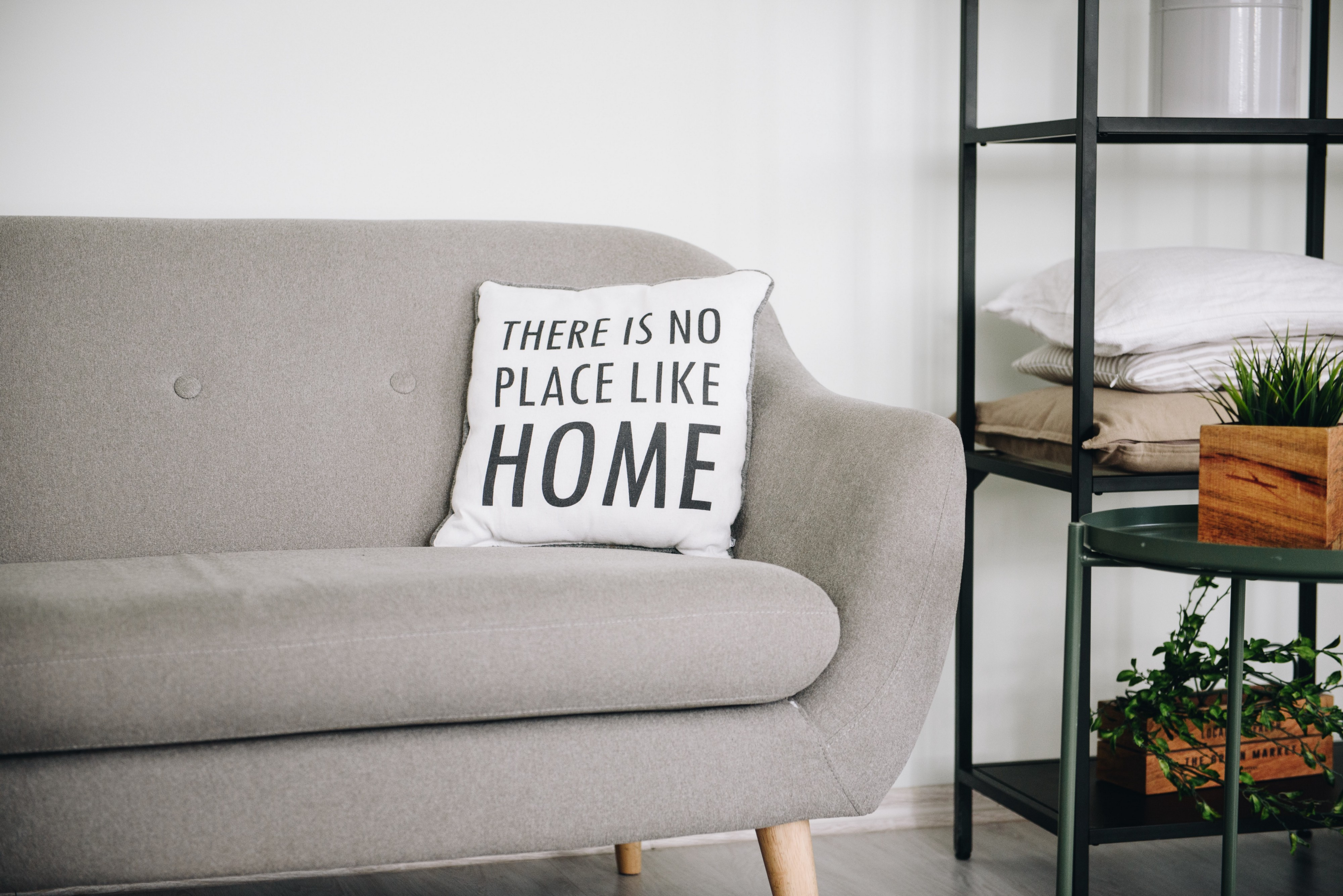 "An quiet room with a grey couch, on which there is a pillow that reads ""There is no place like home"""