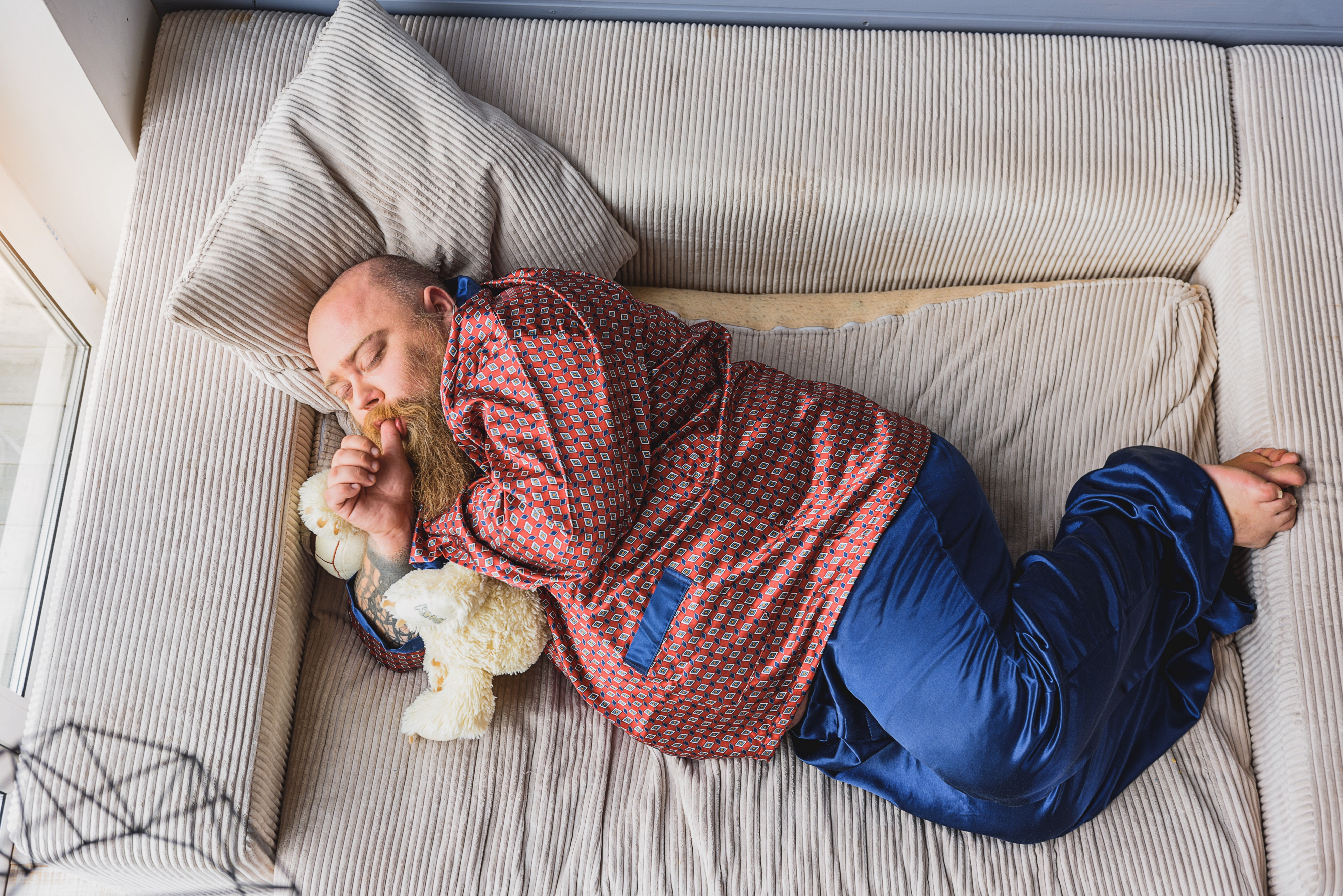 Middle aged fat mad in silk pajamas sleeps on sofa sucking his thumb and holding a teddy bear