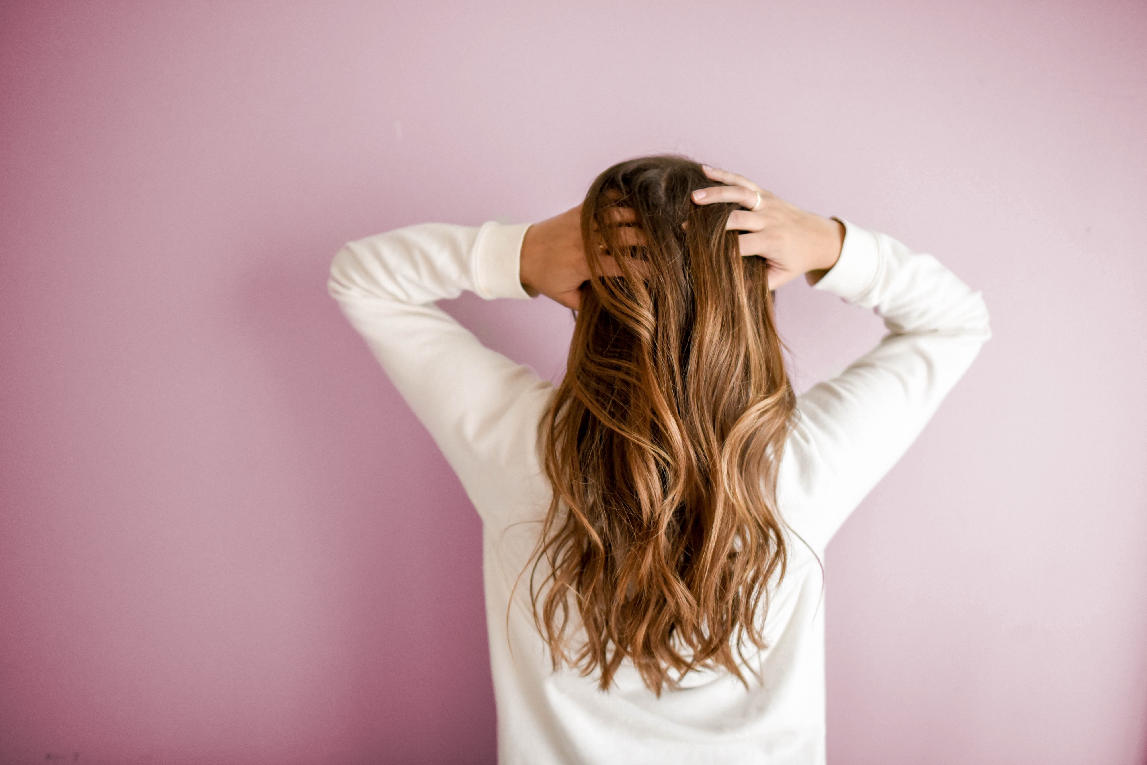 Woman with back to camera grabbing hair in hands
