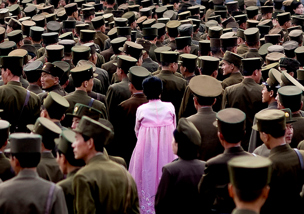 A woman stands in a crowd of North Korean soldiers wearing a pink Hanbok