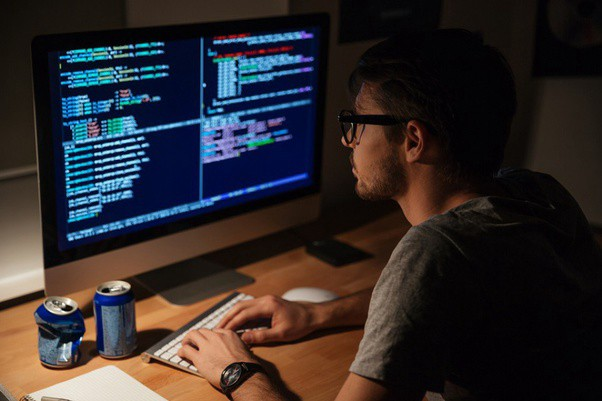 Software Developer sitting in a dimly lit room in front of the computer typing on keyboard and looking at code.