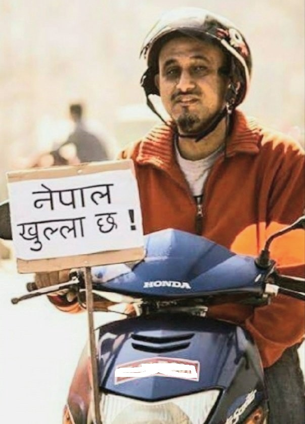 """Ujjwal thapa with a pamplet that says """"Nepal is Open"""""""