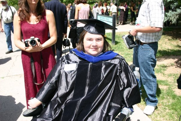 A white woman in a wheelchair is smiling and wearing PhD regalia for graduation
