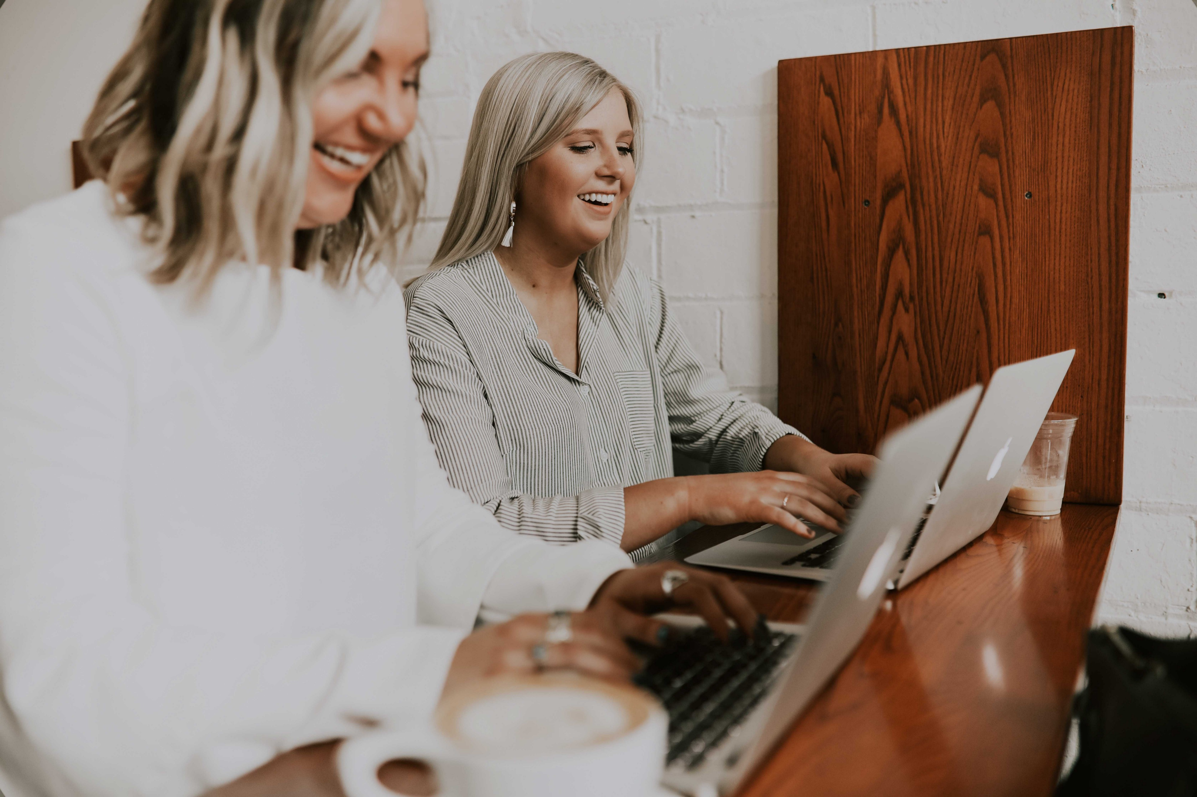 Two young female entrepreneurs working at their laptops