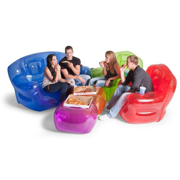 Group of friends eating pizza on colorful inflatable couches, chairs, and ottomans similar to the kind that were popular in the 1990s