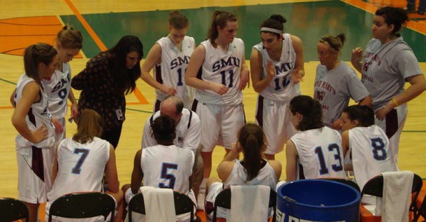 A photo of women on a basketball court, huddled around their couch during a timeout.