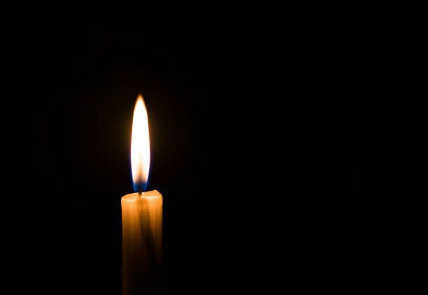 One lit candle with a solid black background