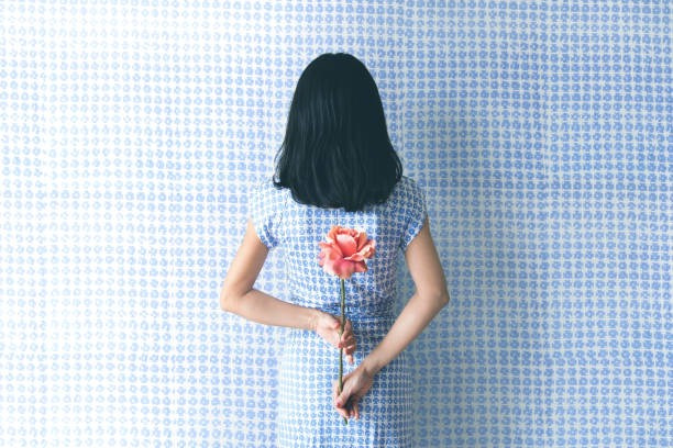 Back of a female-identified person holding a flower behind her back. She has shoulder length black hair. She is wearing a black and white dress, in front of a background that matches.