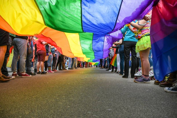 Image description: Many people are lined up holding a very long rainbow banner on a street. The photo is taken from below the banner so only the lower bodies of the people are in the picture.