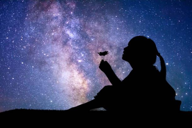 Silhouette of a child holding a flower and seated looking up at night sky full of stars and the Milky Way.
