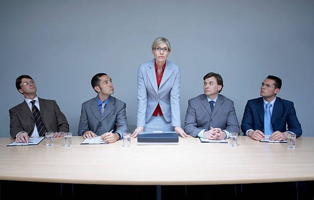 Picture of woman standing in a board room, flanked by men seated on either side.