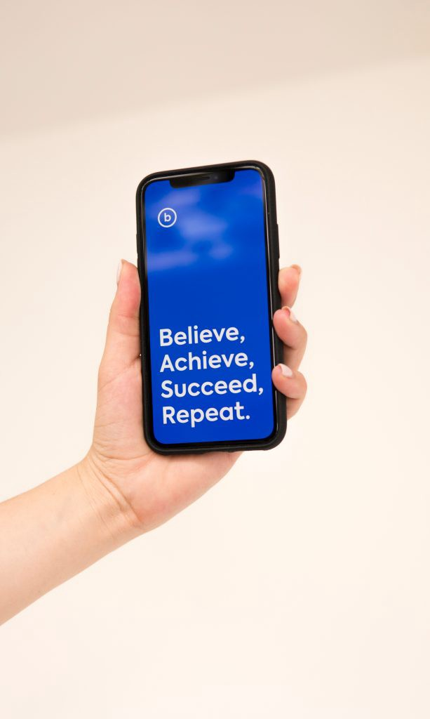 A hand holding a cell phone with the words believe, achieve, succeed, repeat.