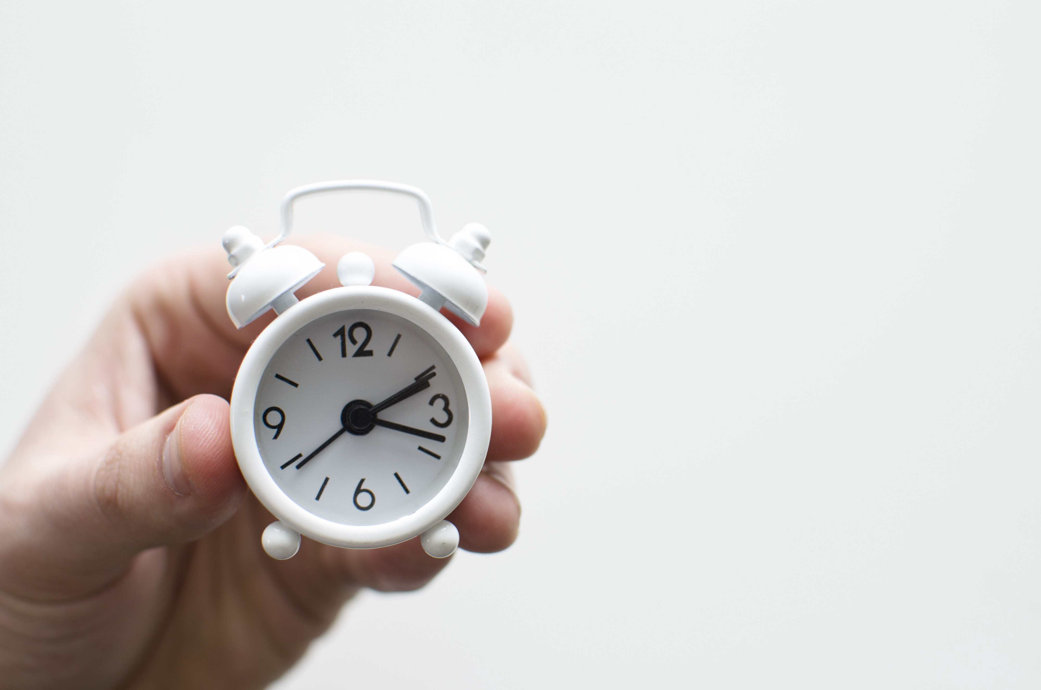 Time management skills are important for small business owners. A hand holds a small, ticking clock; time is in his hands.