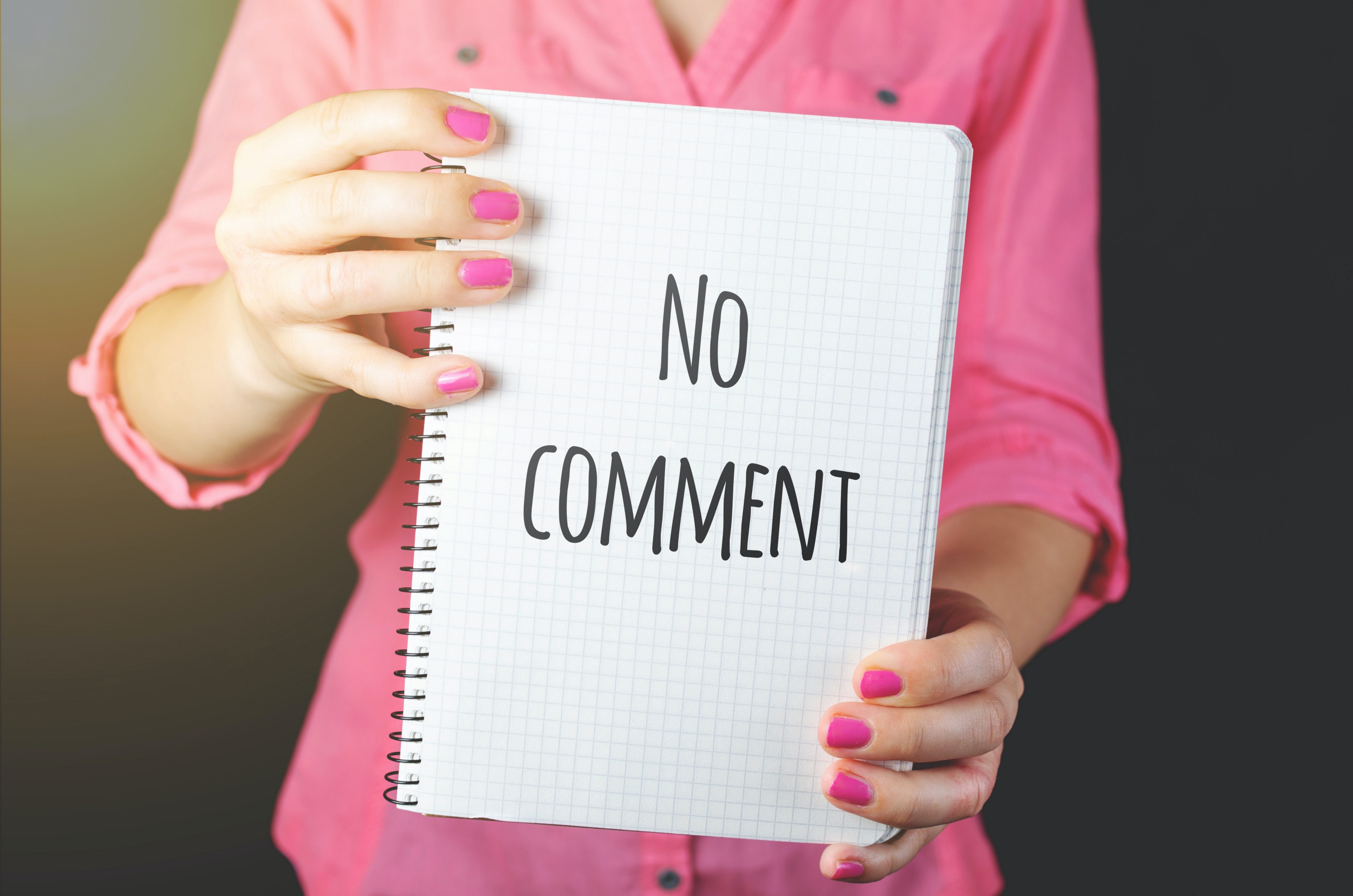 """A woman holding up a notebook with the words, """"No Comment"""", written on the page."""